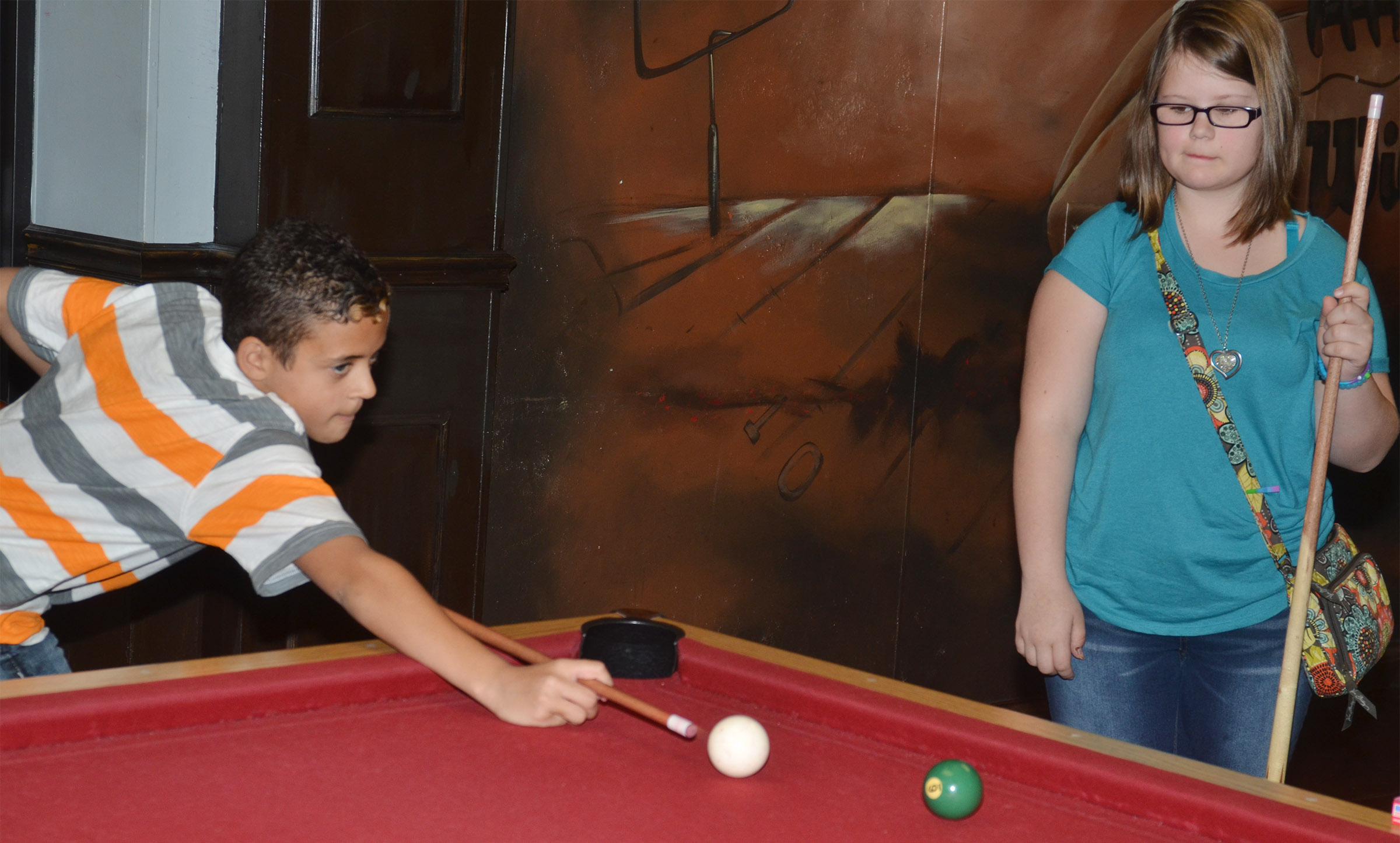 CMS fifth-graders Tucker Cartwright, at left, and Kylee Cox play pool at the Student Activities Center.