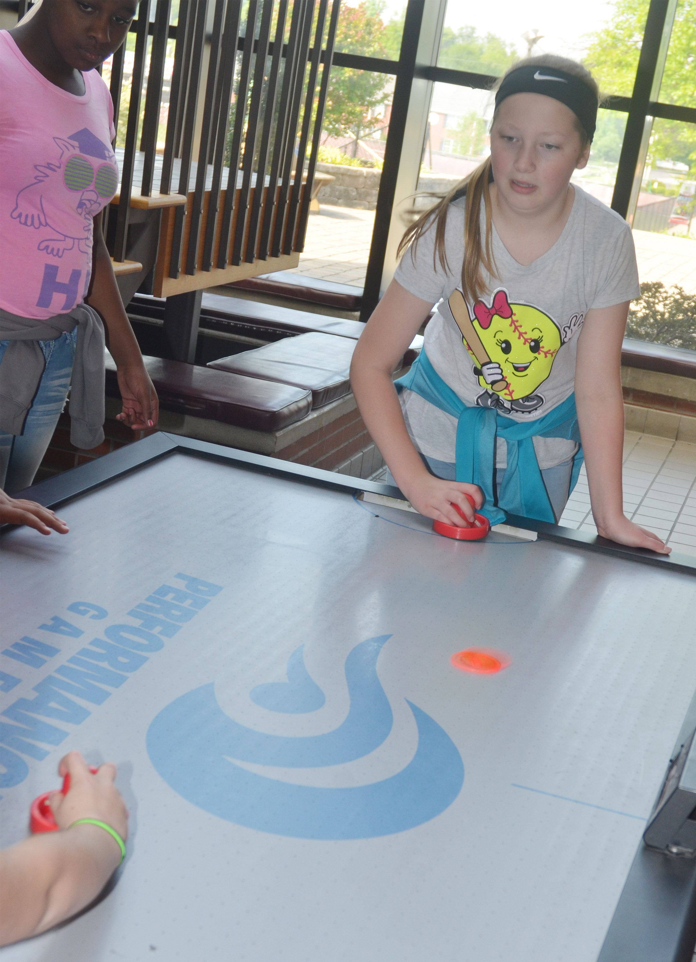 CMS fifth-grader Ava Hughes plays air hockey with her classmates at the Student Activities Center.