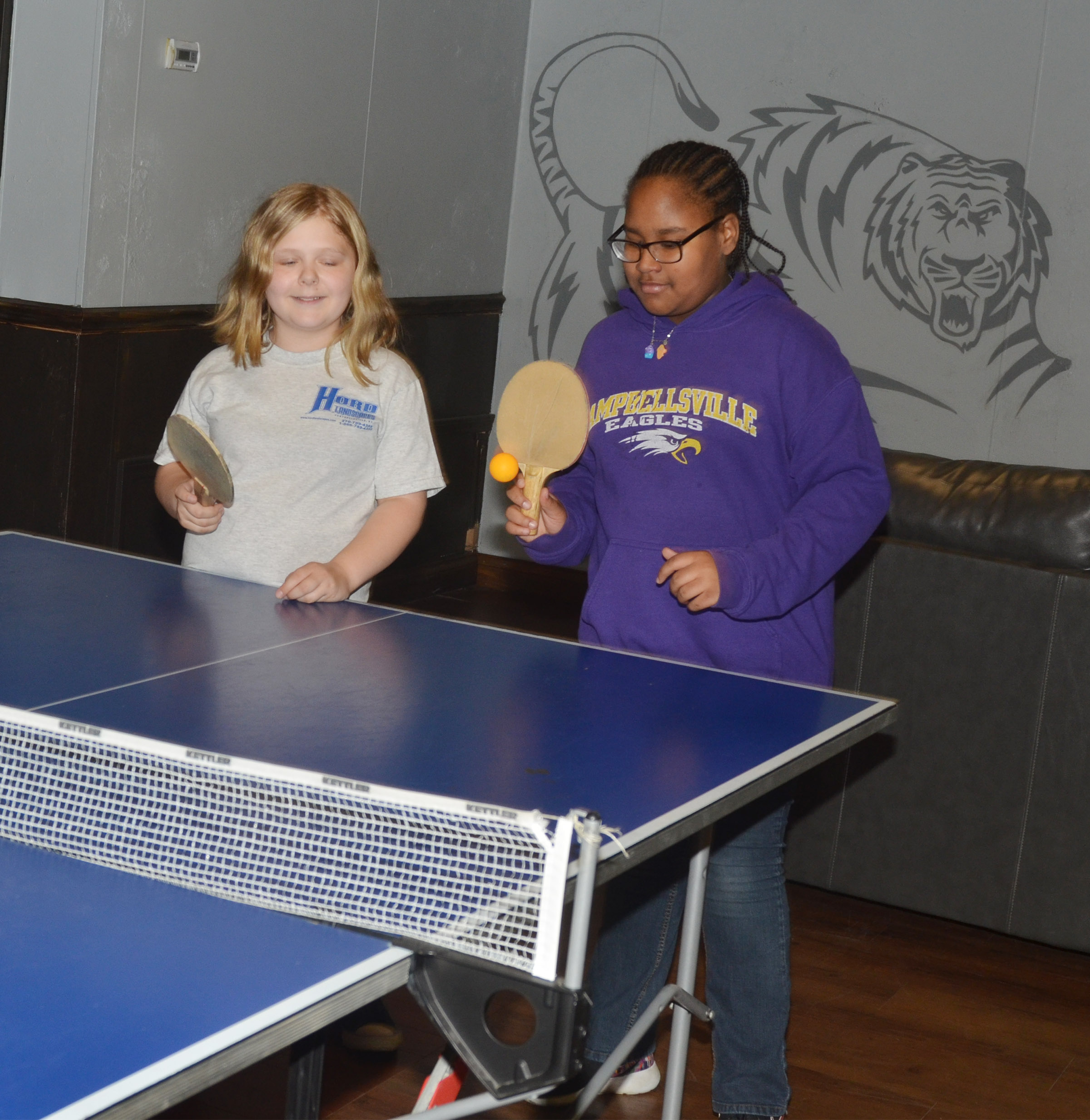 CMS fifth-graders Alexis Sharp, at left, and KyAshia Mitchell play ping pong at the Student Activities Center.