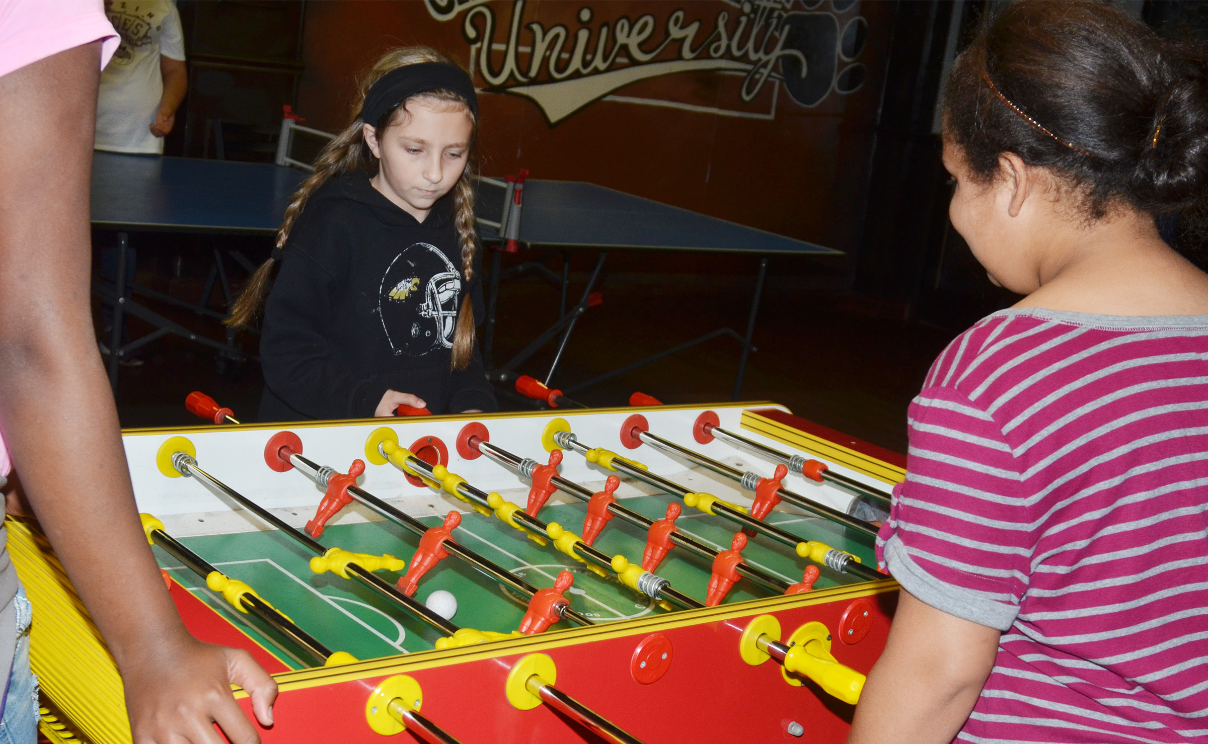 CMS fifth-grader Heather Leggett plays foosball with her classmates at the Student Activities Center.