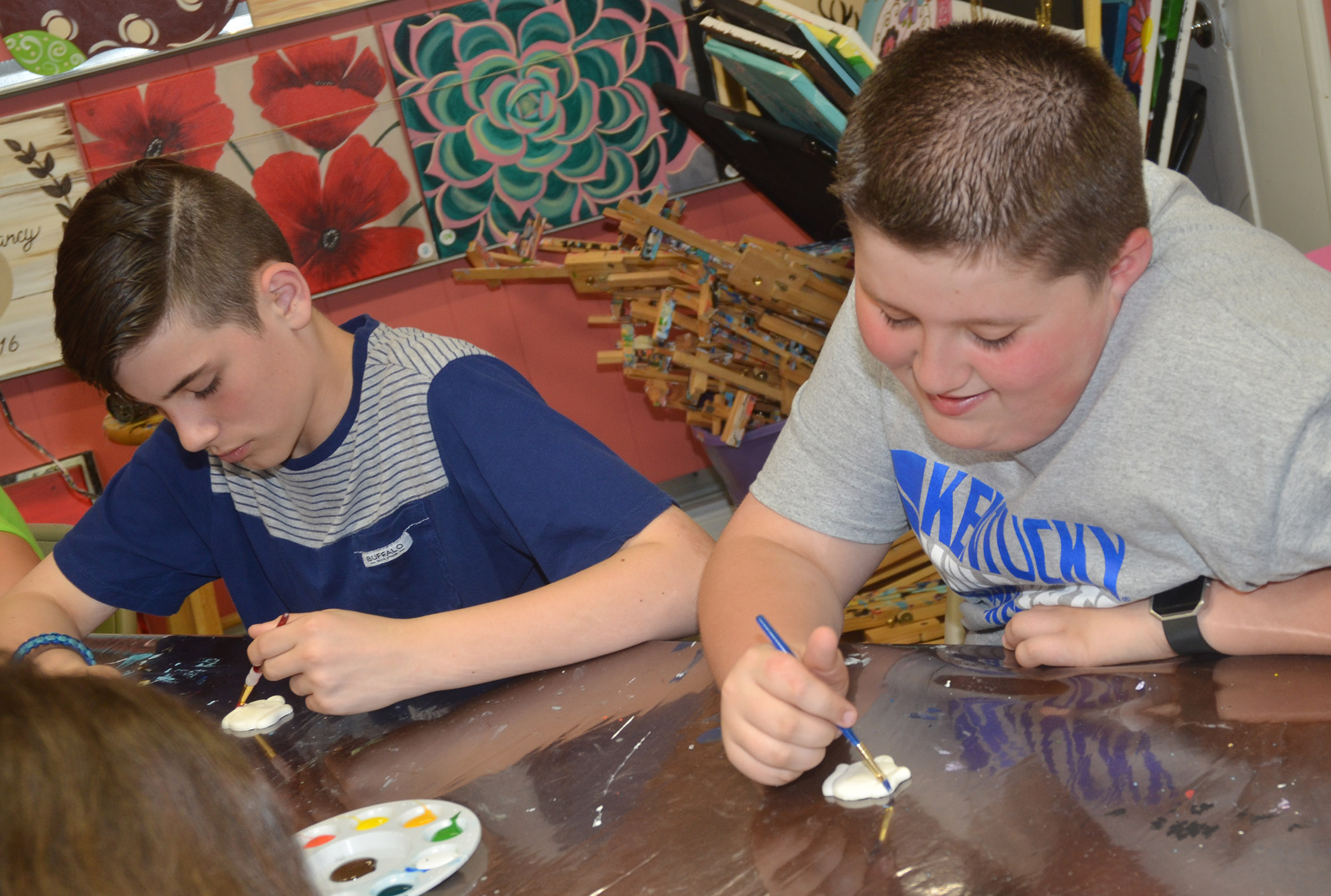 CMS fifth-graders Isaac Garrison, at left, and Luke McDonald paint figurines.