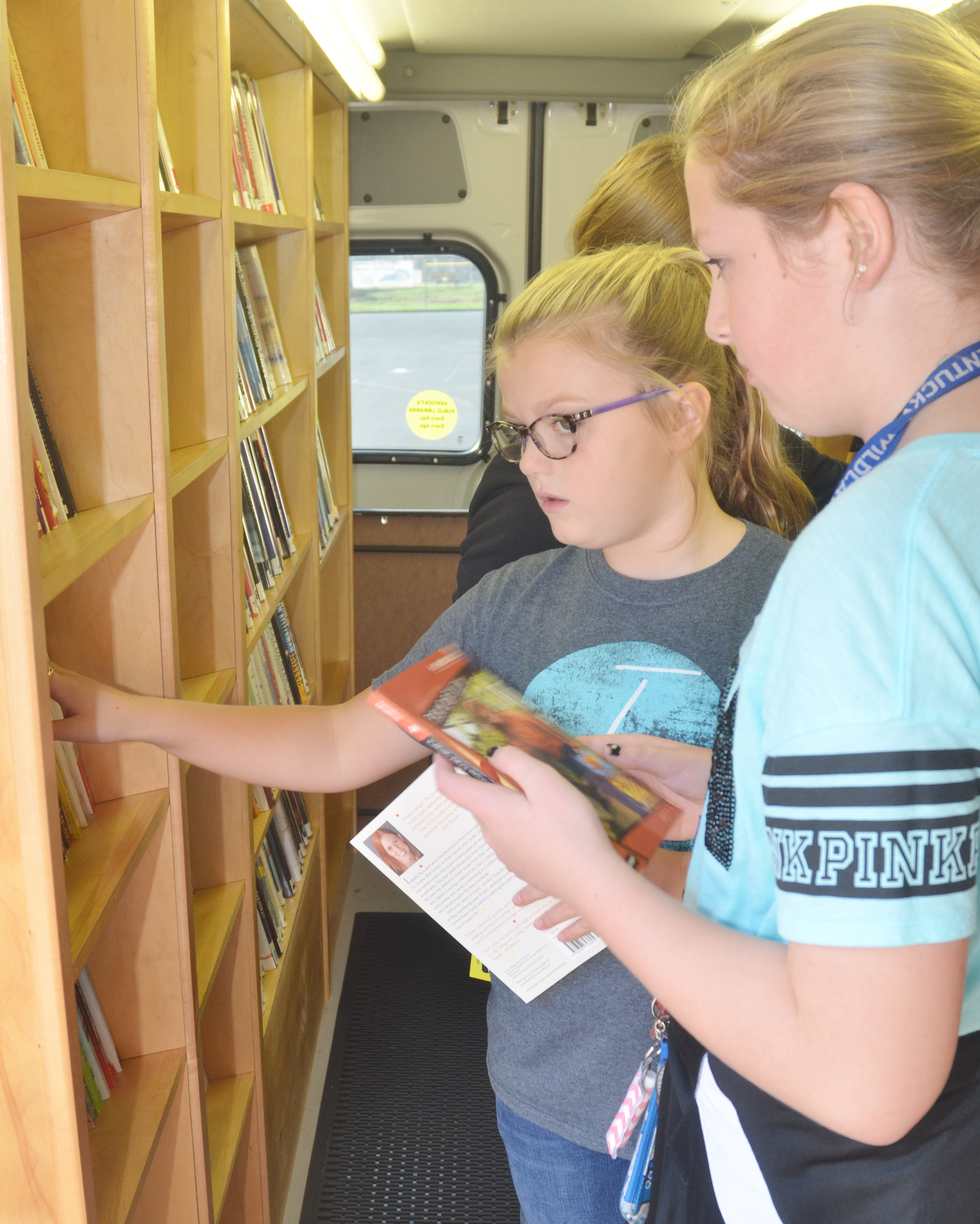 CMS sixth-graders Ellington Gowin, at left, and Ava Hughes look for books.