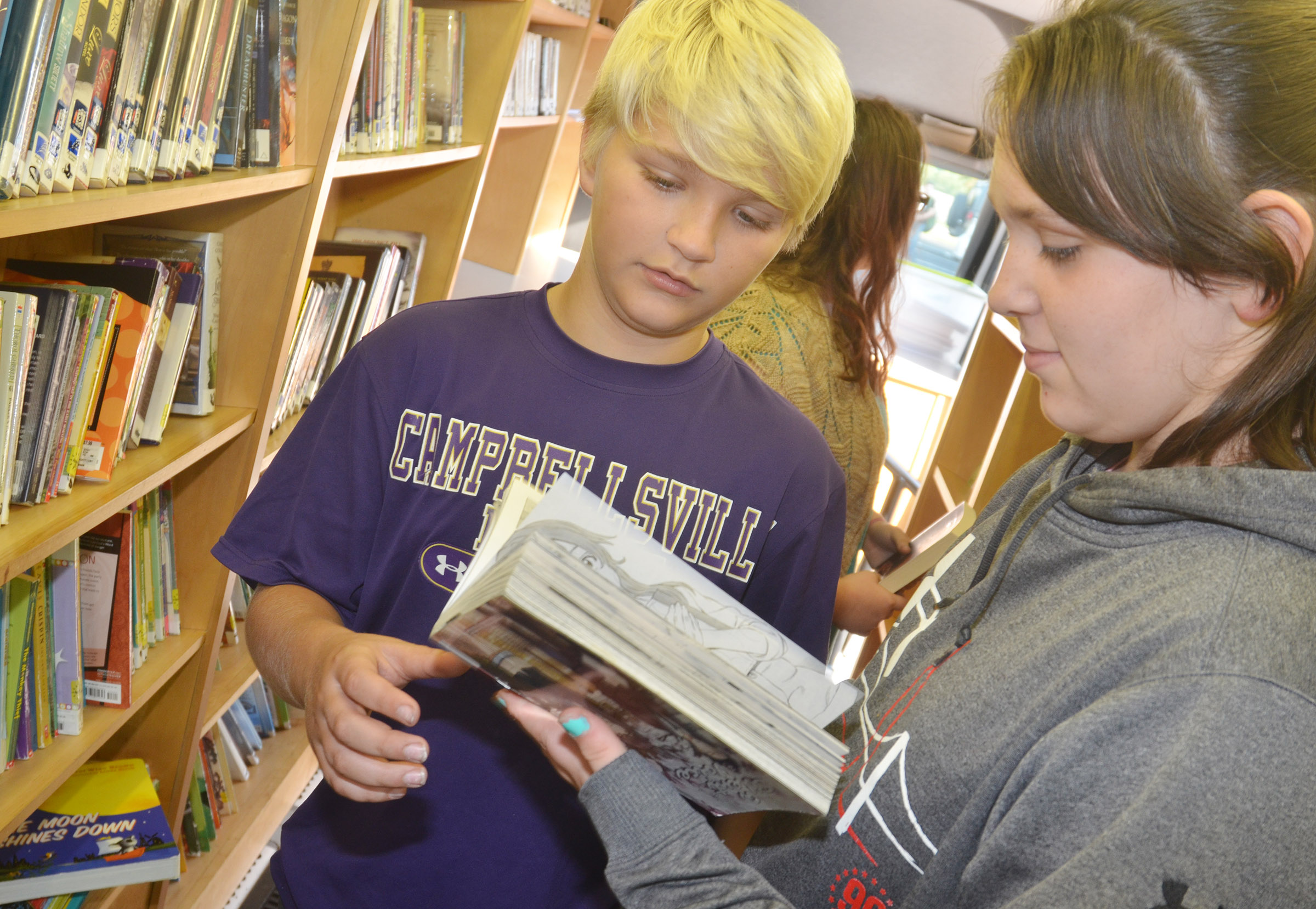 CMS sixth-graders Dakota Tungate, at left, and Allie Compton look at a book together.