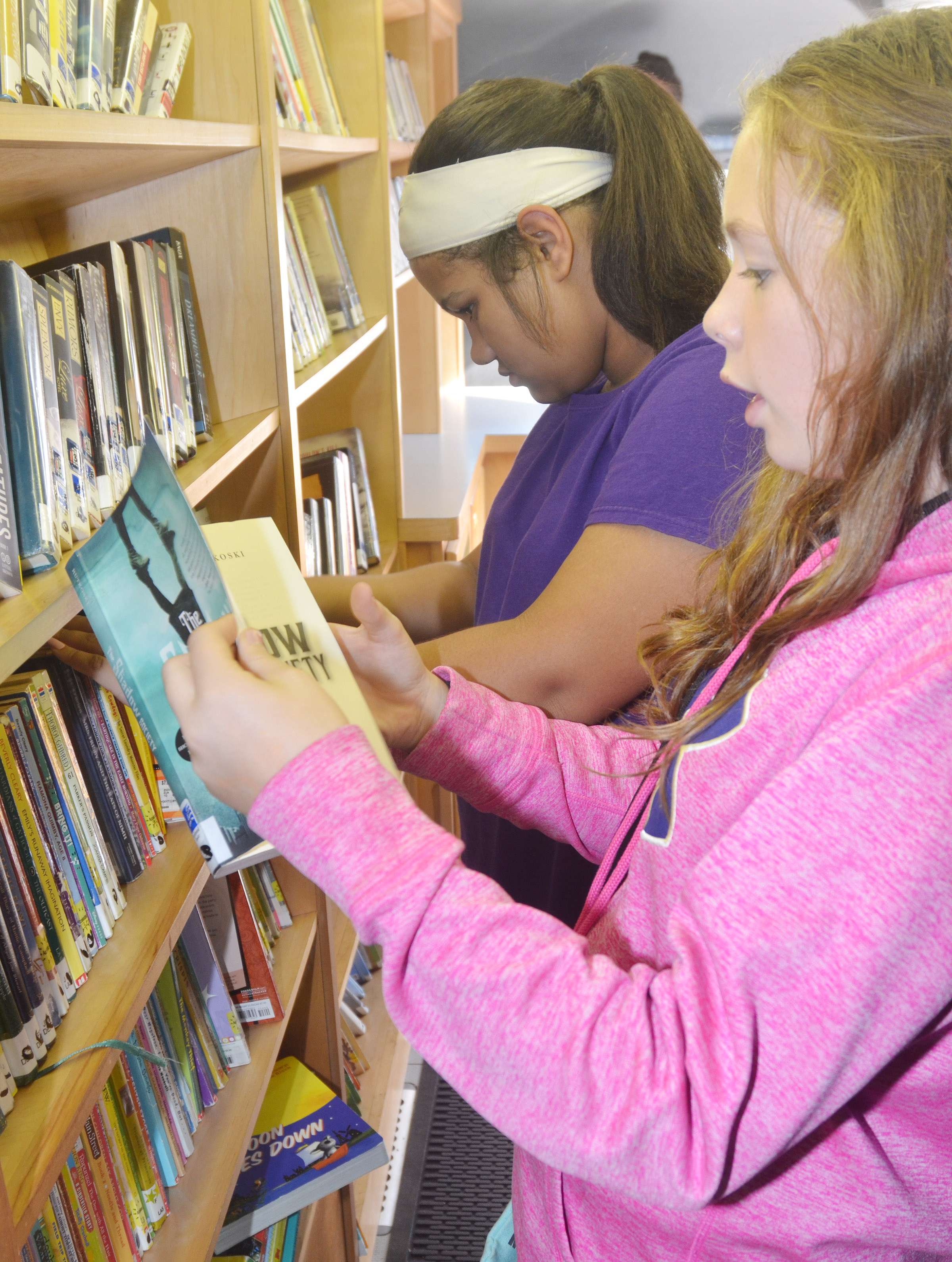 CMS sixth-graders Kehleigh Vaught, at left, and CheyAnn Edwards look at books.