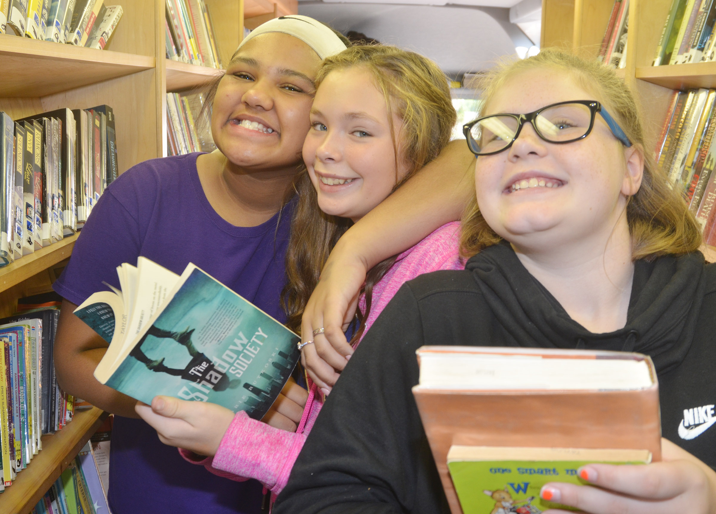 From left, CMS sixth-graders Kehleigh Vaught, CheyAnn Edwards and Piper Ritchie choose books to check out.