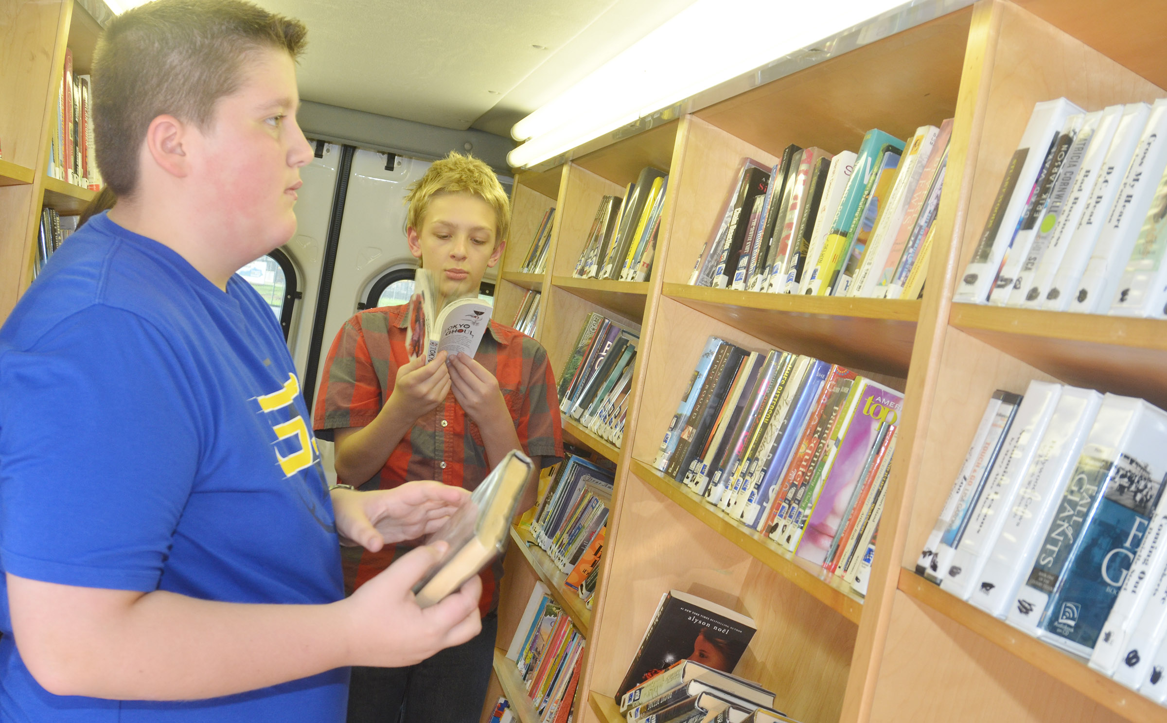 CMS sixth-graders Luke McDonald, at left, and Jacob Releford choose books to check out.