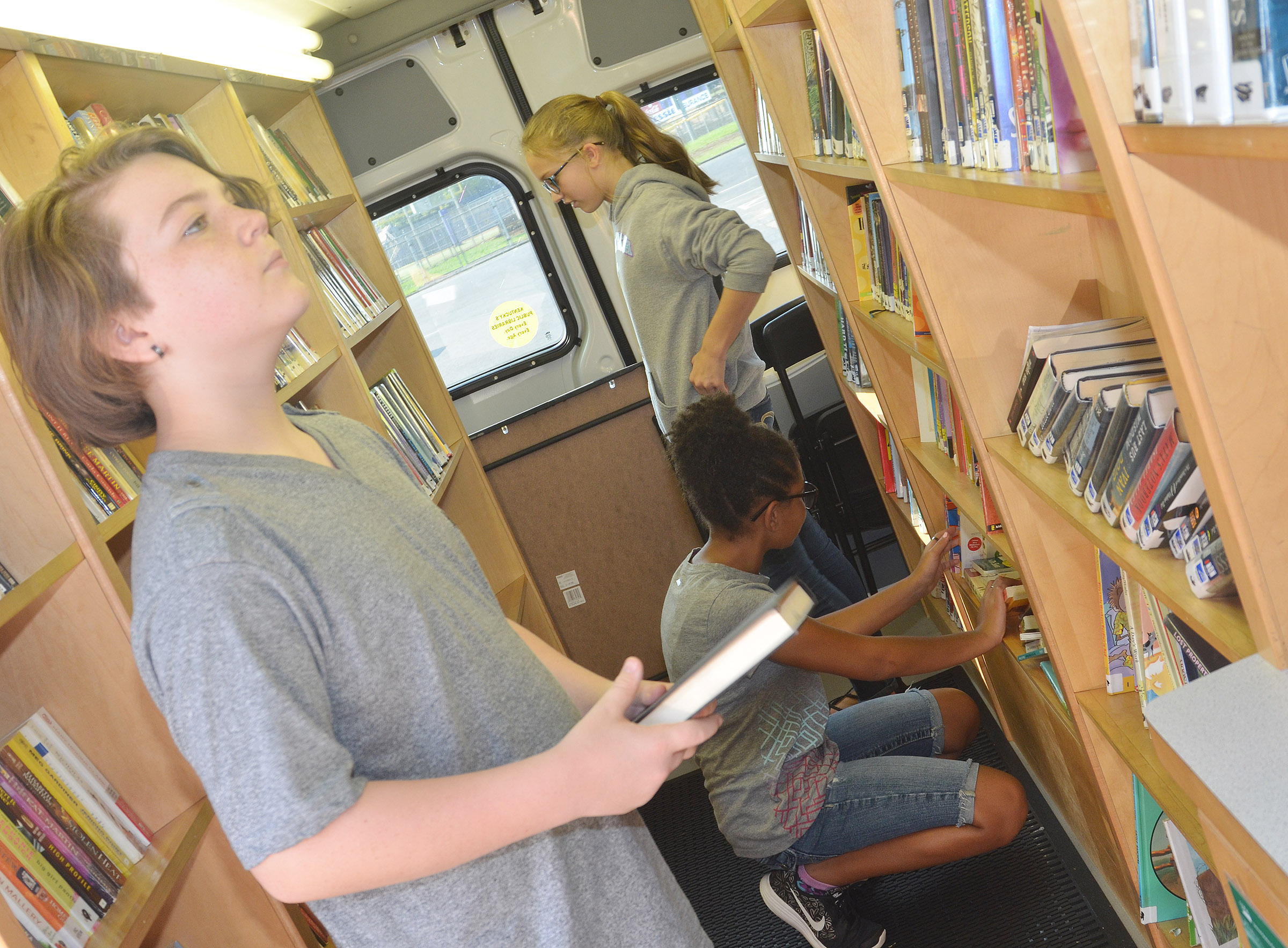CMS sixth-graders, from left, Kayden Birdwell, Keely Thompson and Chloe Thompson look at books.