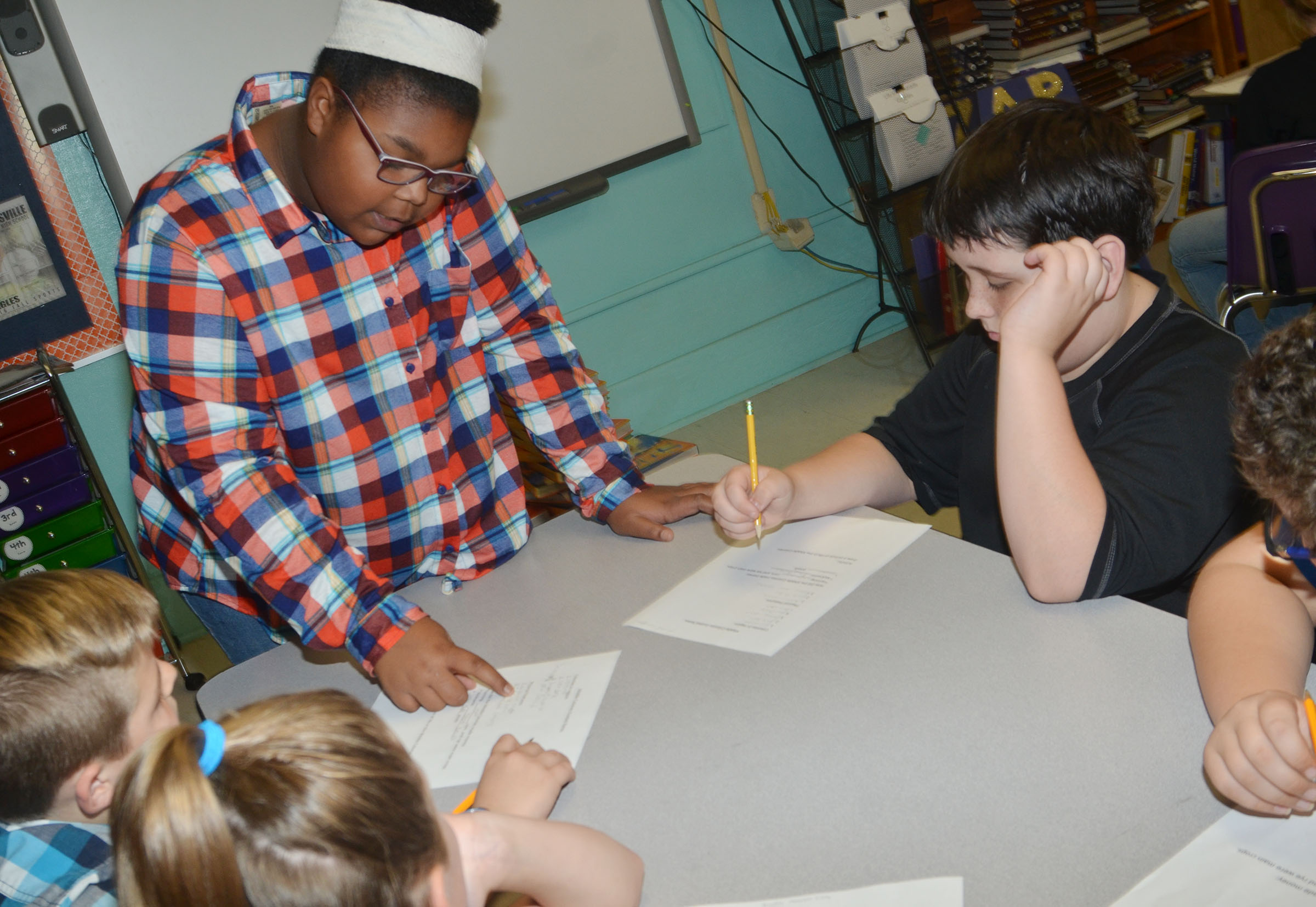CMS eighth-grader Destany Lane helps fifth-graders with their notes on the middle colonies.
