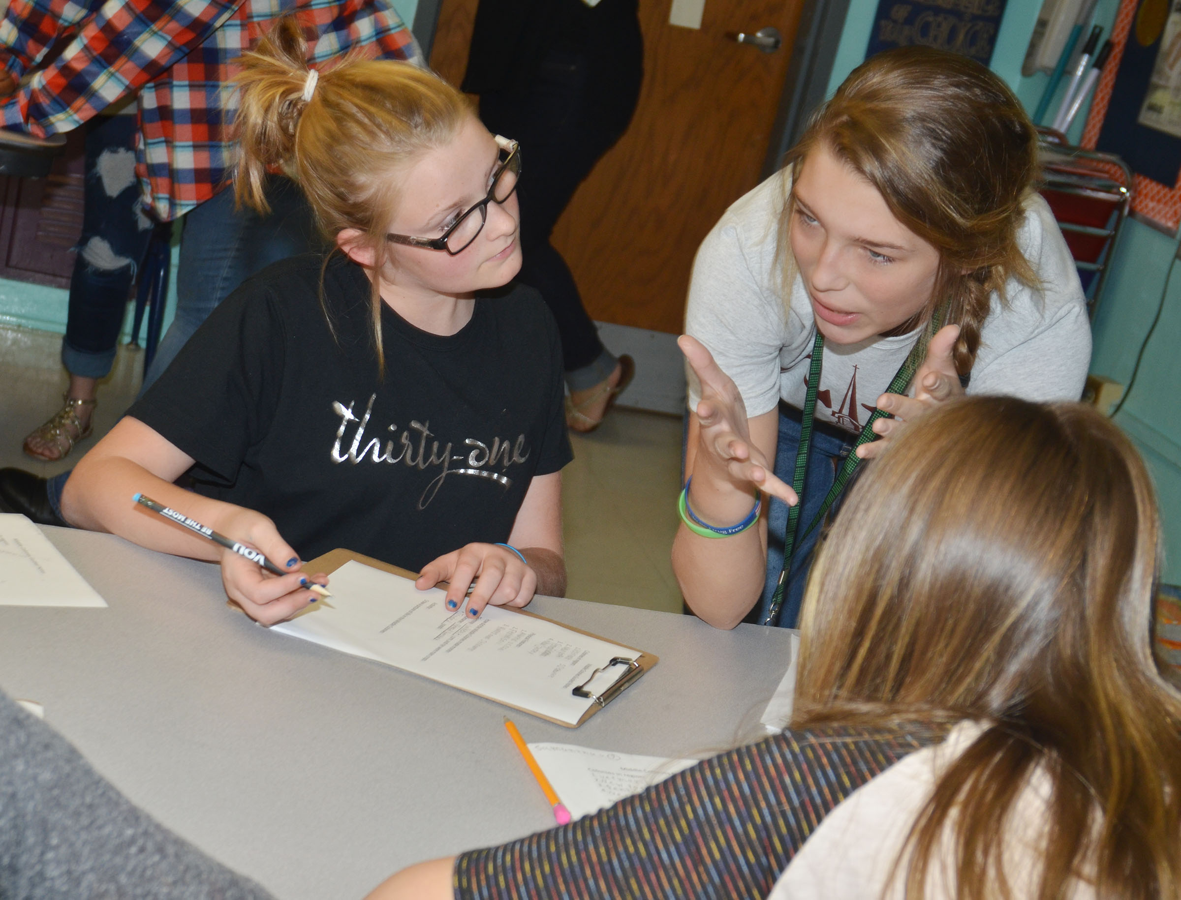 CMS eighth-grader Autumn Harvey discusses the middle colonies with fifth-grader Summer Jacobs.