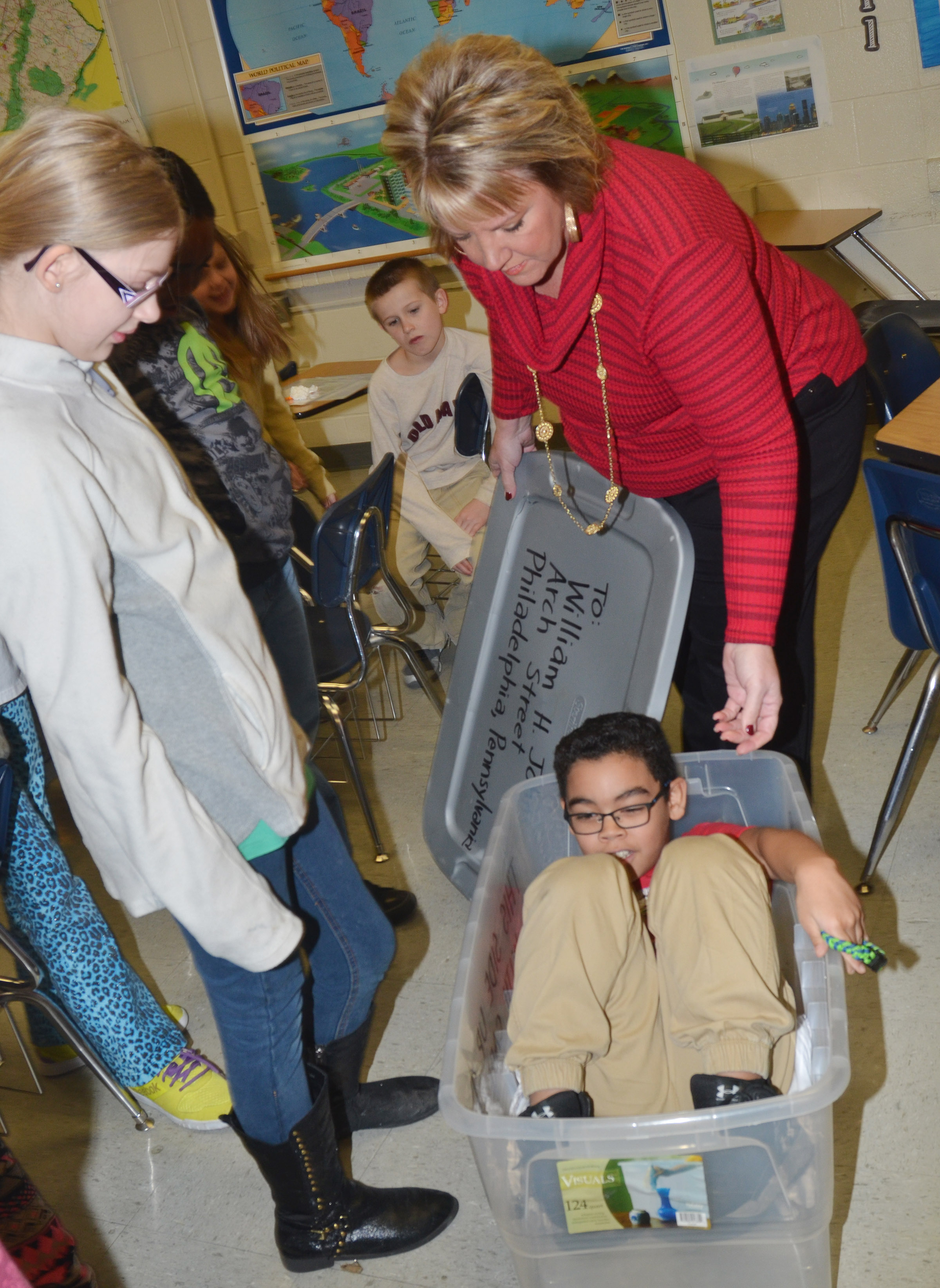 CMS social studies teacher Kaye Agathen helps fourth-grader Gabriel Noyola out of the box used as an example of the one Henry Brown used to mail himself to freedom.