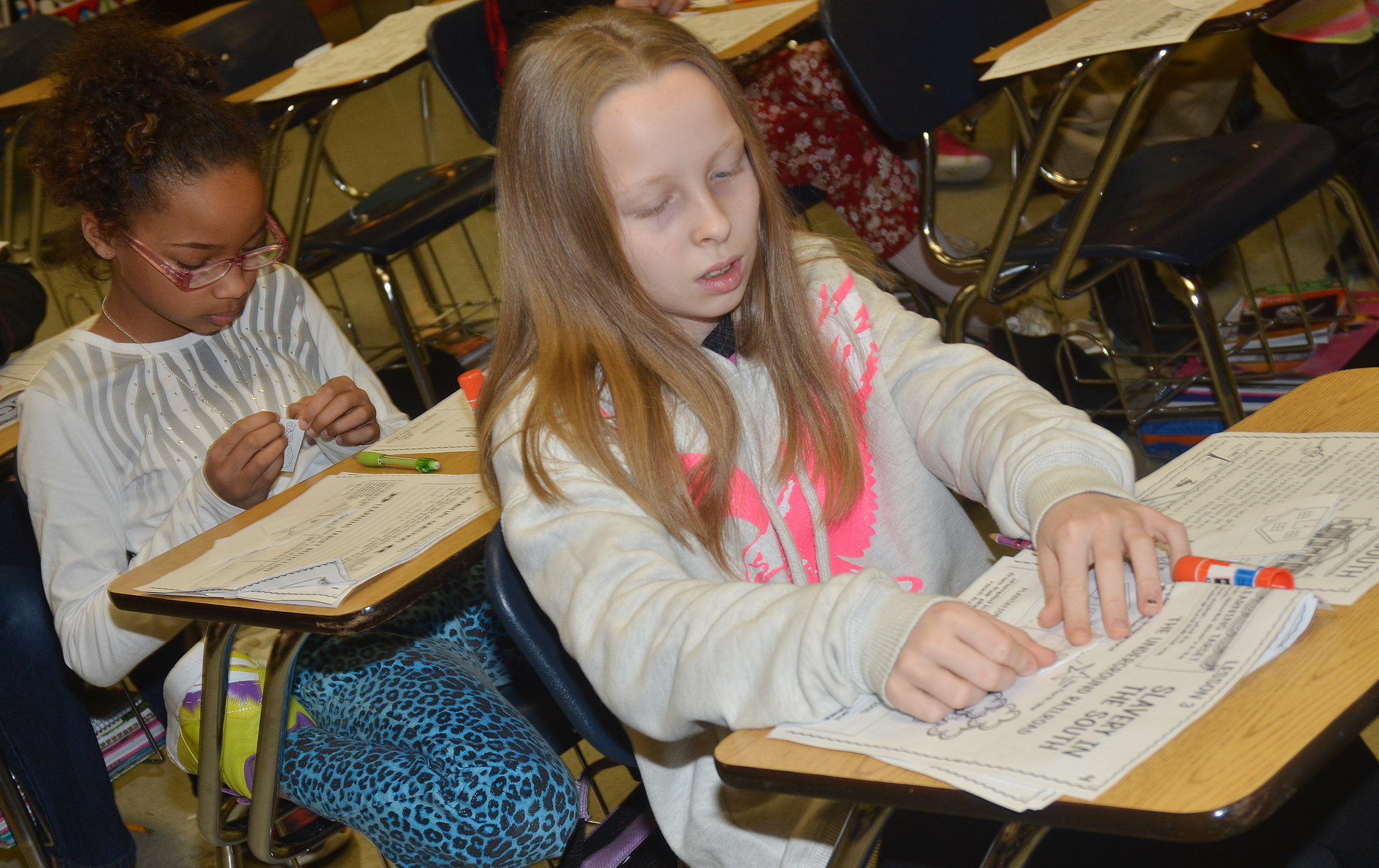 CMS fourth-graders Lillian Sears, at left, and Lily Sallee complete worksheets as they learn about slavery.