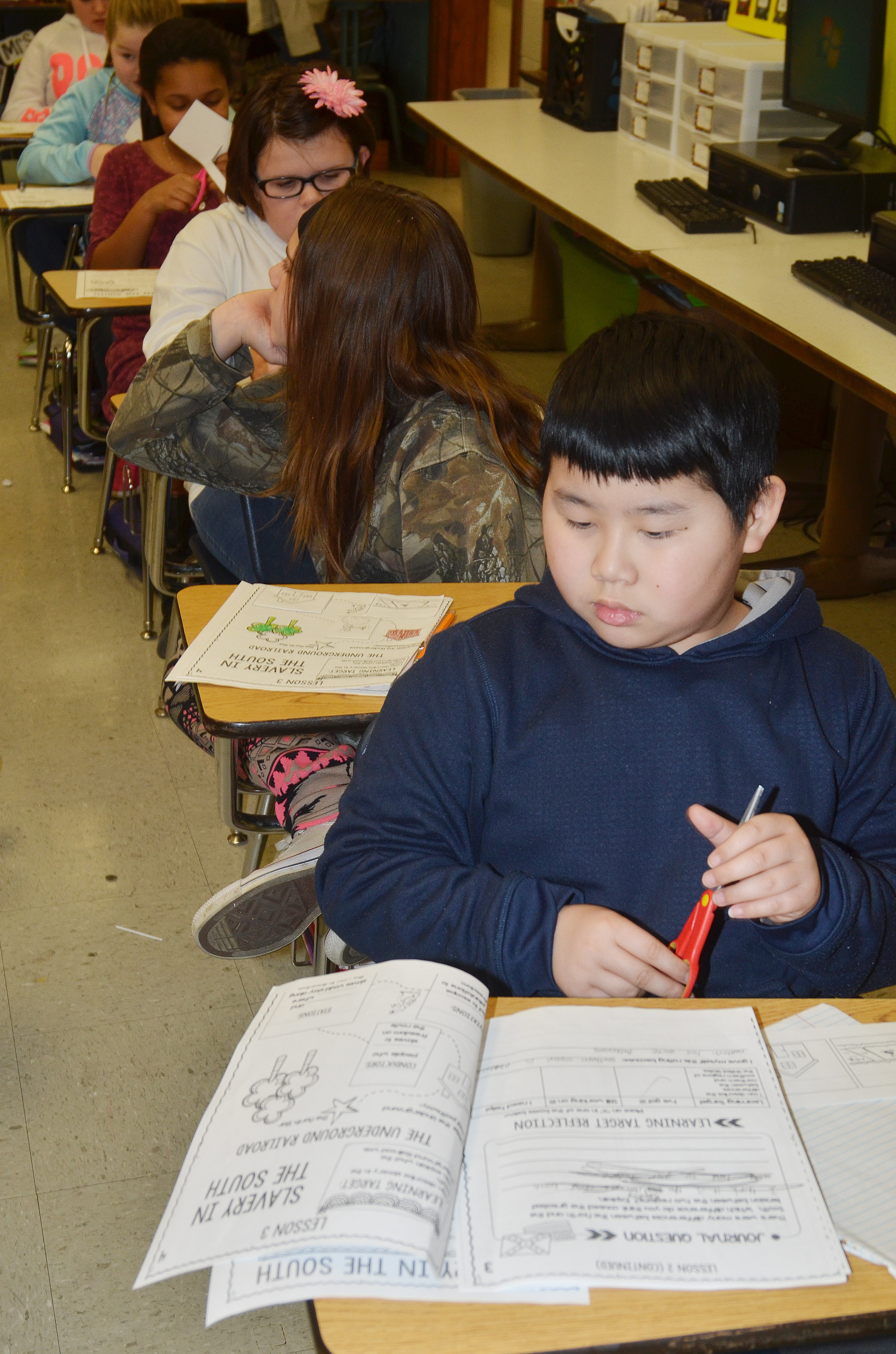 CMS fourth-grader Zhi Chen completes a worksheet as he learns about slavery.