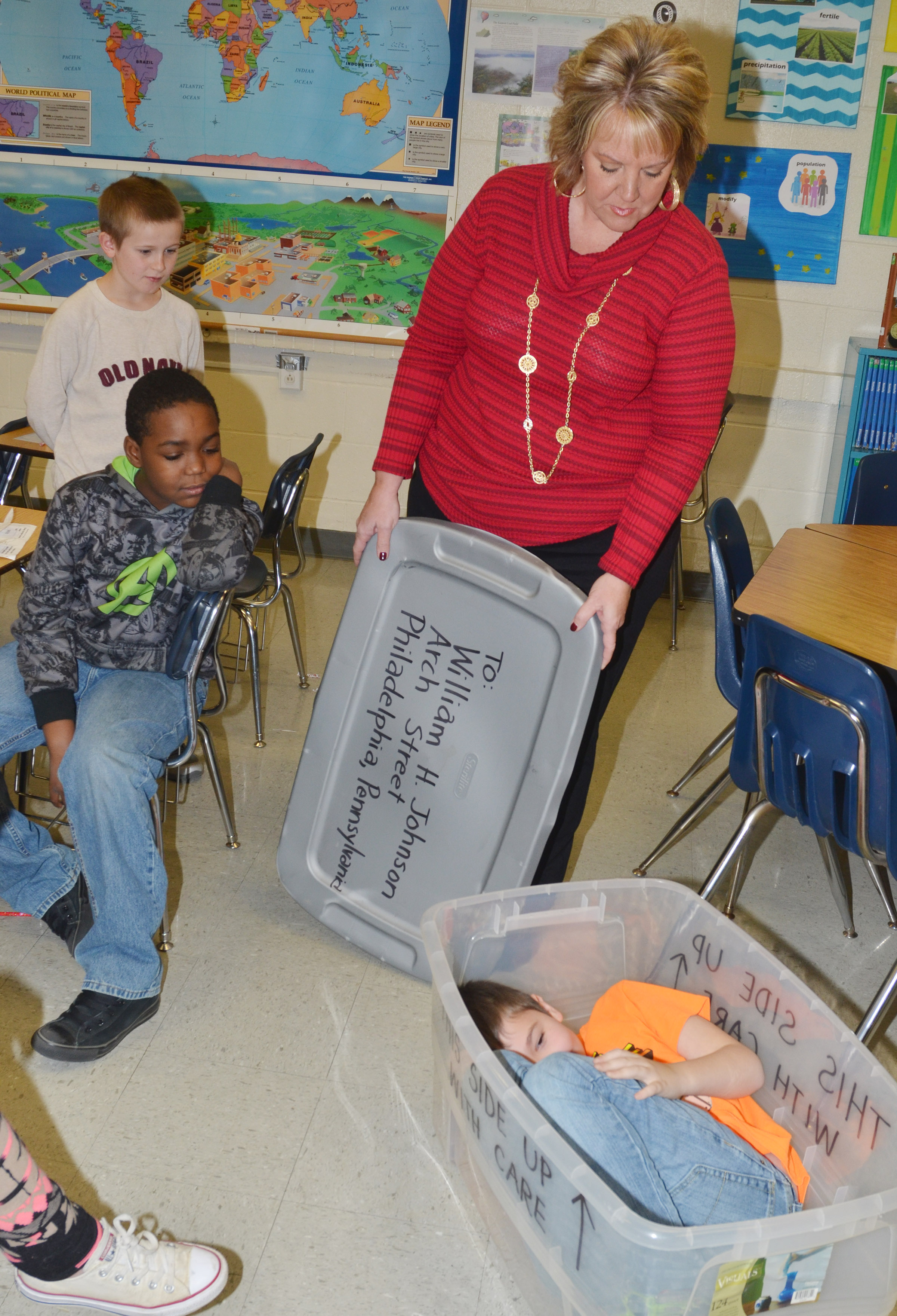 CMS fourth-grader Michael Abel hides in a box like the one Henry Brown used to mail himself to freedom, as social studies teacher Kaye Agathen watches.