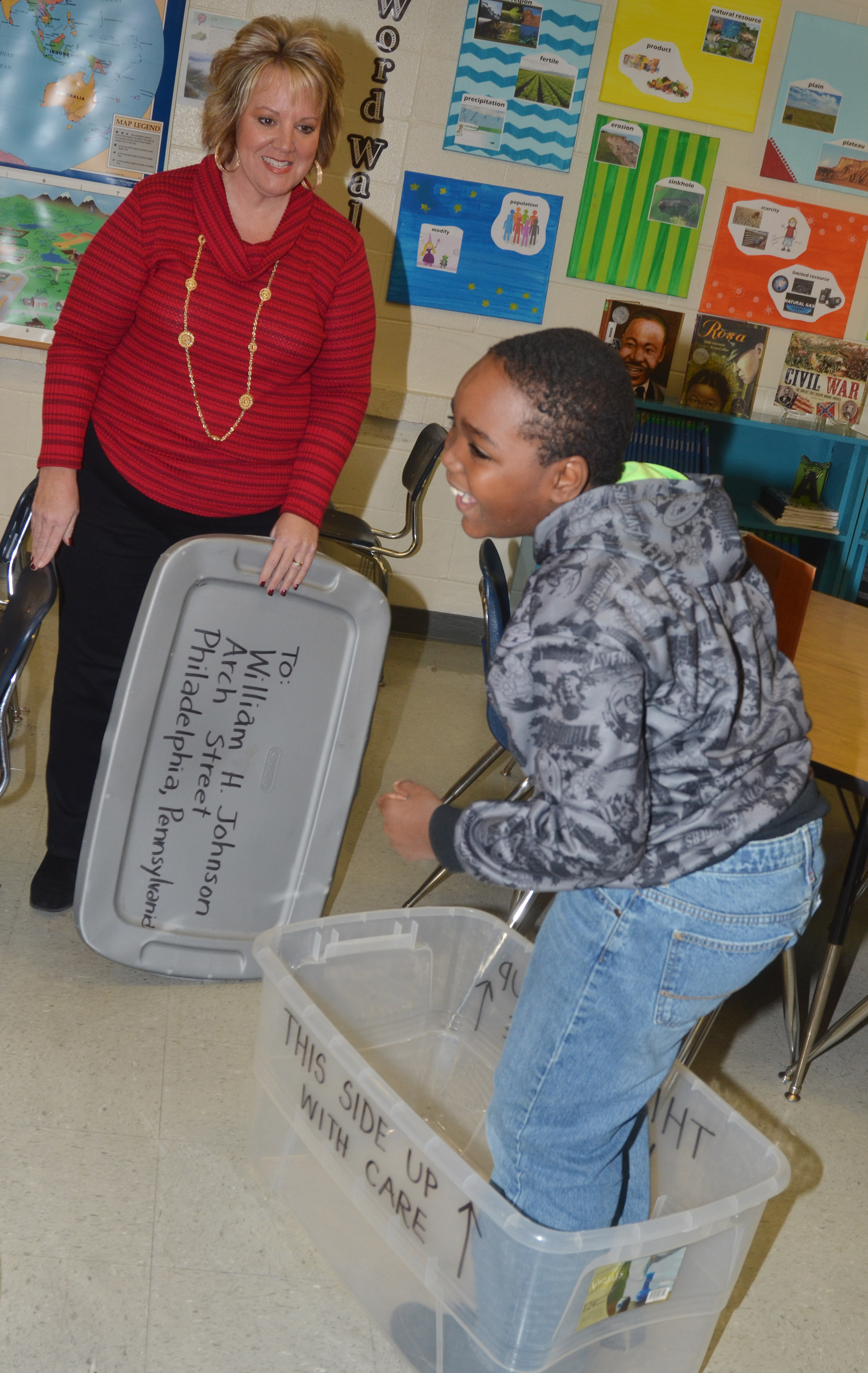 CMS fourth-grader Deason Smith laughs as he tries to fit inside a box like the one Henry Brown used to mail himself to freedom, as social studies teacher Kaye Agathen watches.