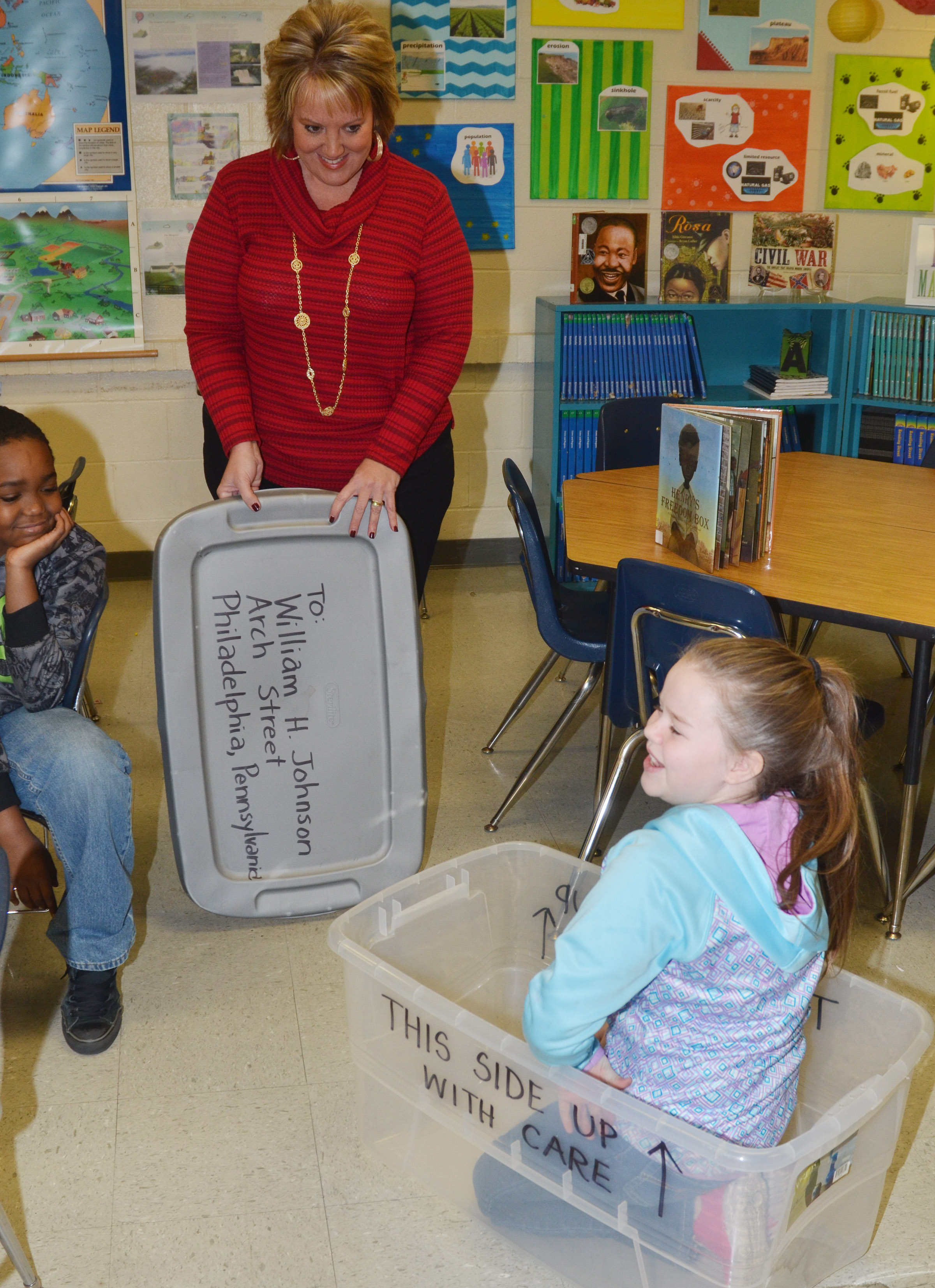 CMS fourth-grader Miley Hash laughs as she tries to fit inside a box like the one Henry Brown used to mail himself to freedom, as social studies teacher Kaye Agathen watches.
