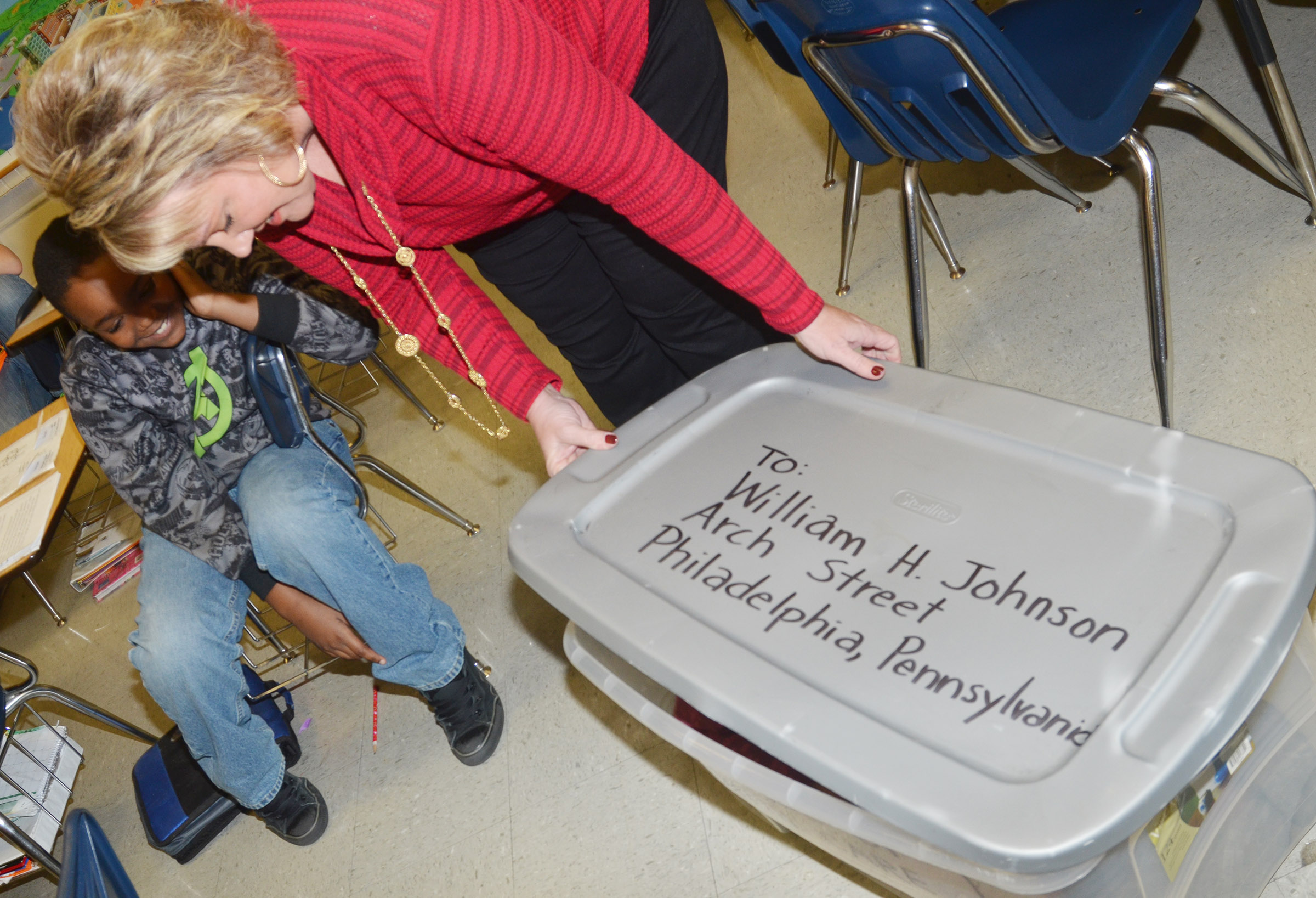CMS social studies teacher Kaye Agathen looks inside a box in which one of her students is hiding. Henry Brown used a box like this one to mail himself to freedom.