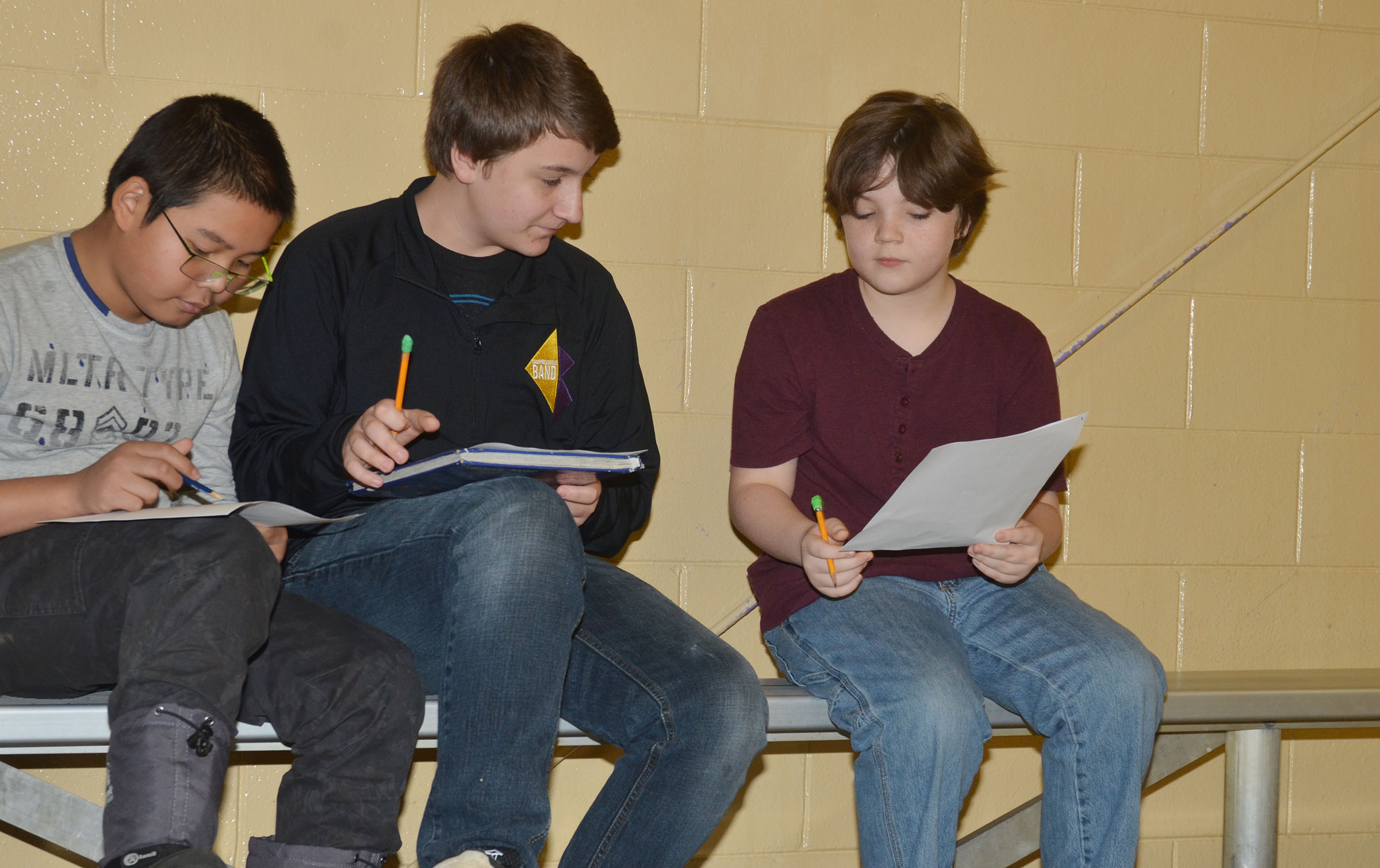 CMS fifth-graders Kewin Dong, at left, and Kayden Birdwell, at right, work with eighth-grader Nick Drew to discuss the American Revolution.