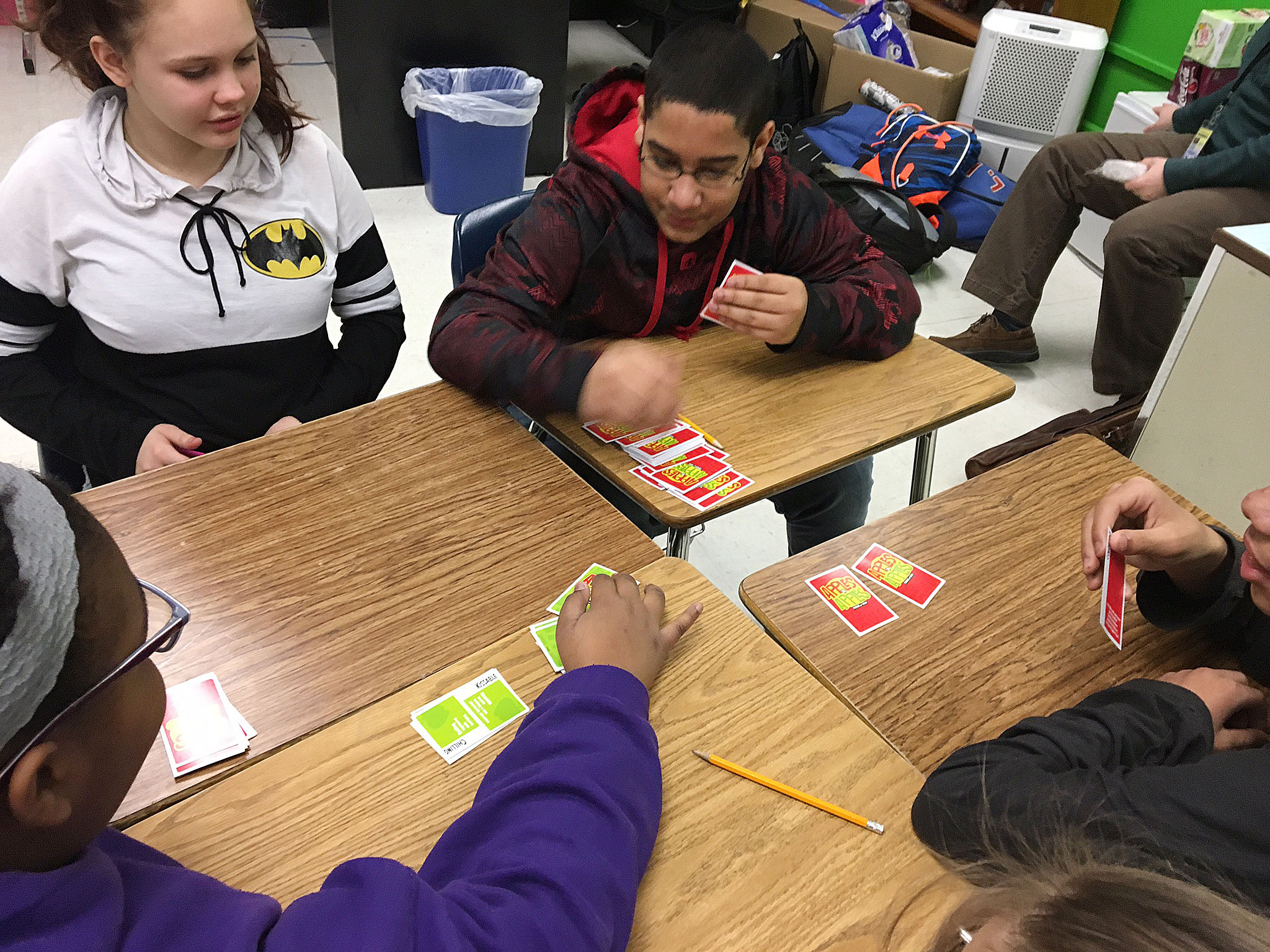 CMS eighth-graders Mystique Jones, at left, and Tyreece Washington play Apples to Apples with their classmates.