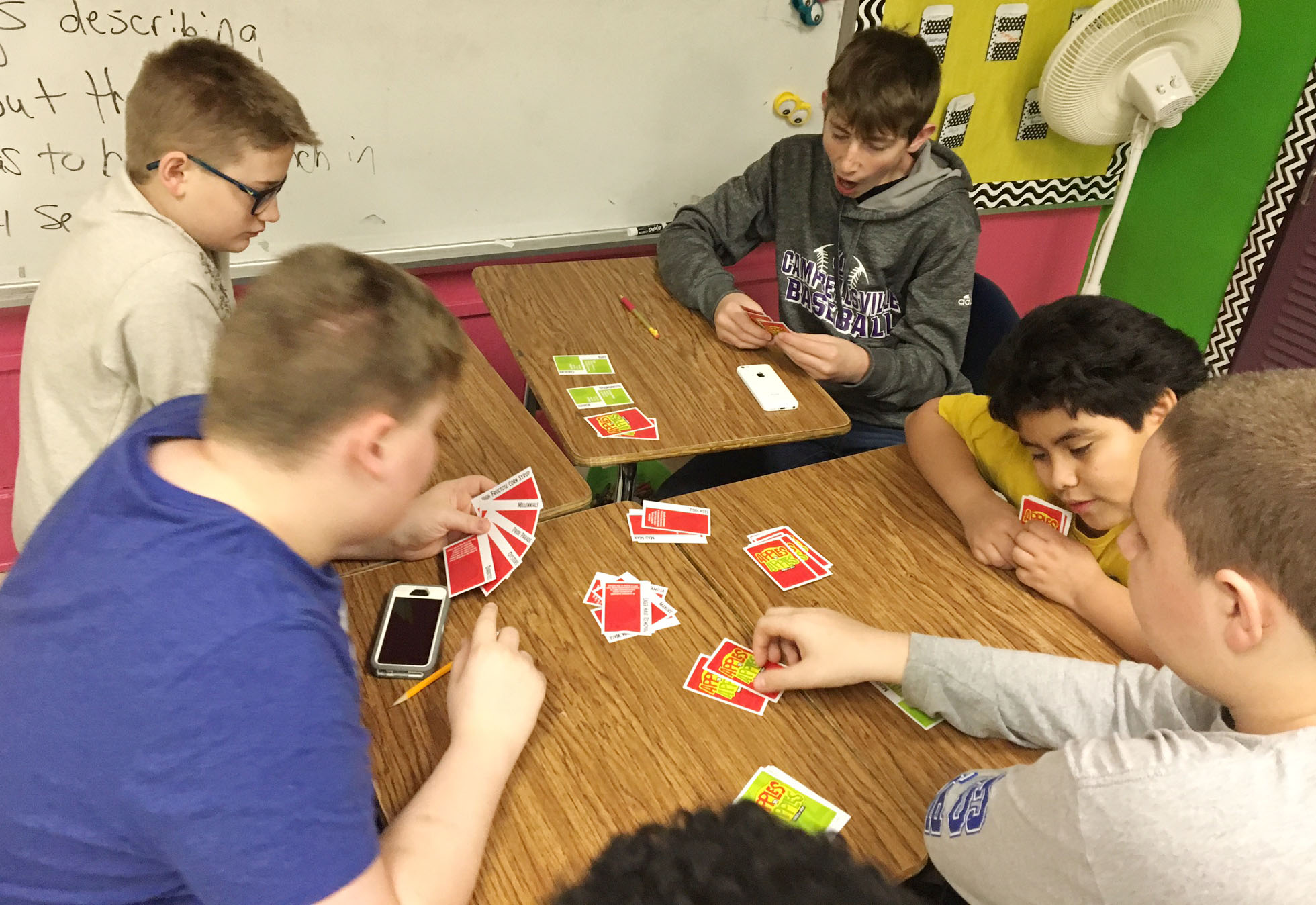 CMS students play Apples to Apples. Clockwise from left are seventh-grader Blake Settle, sixth-grader Brady Hoosier, seventh-grader Waylon Franklin and fifth-grader Alex Martinez play the game with their classmates.