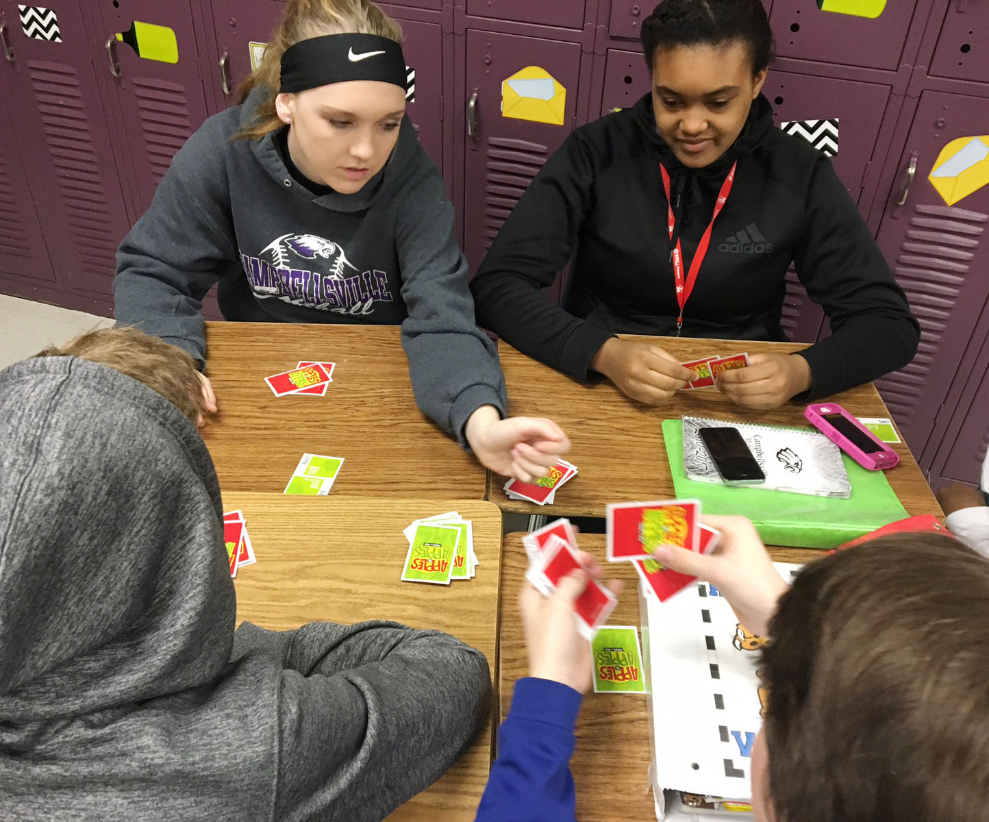 CMS eighth-graders Catlyn Clausen, at left, and Kelsey King play Apples to Apples with their classmates.