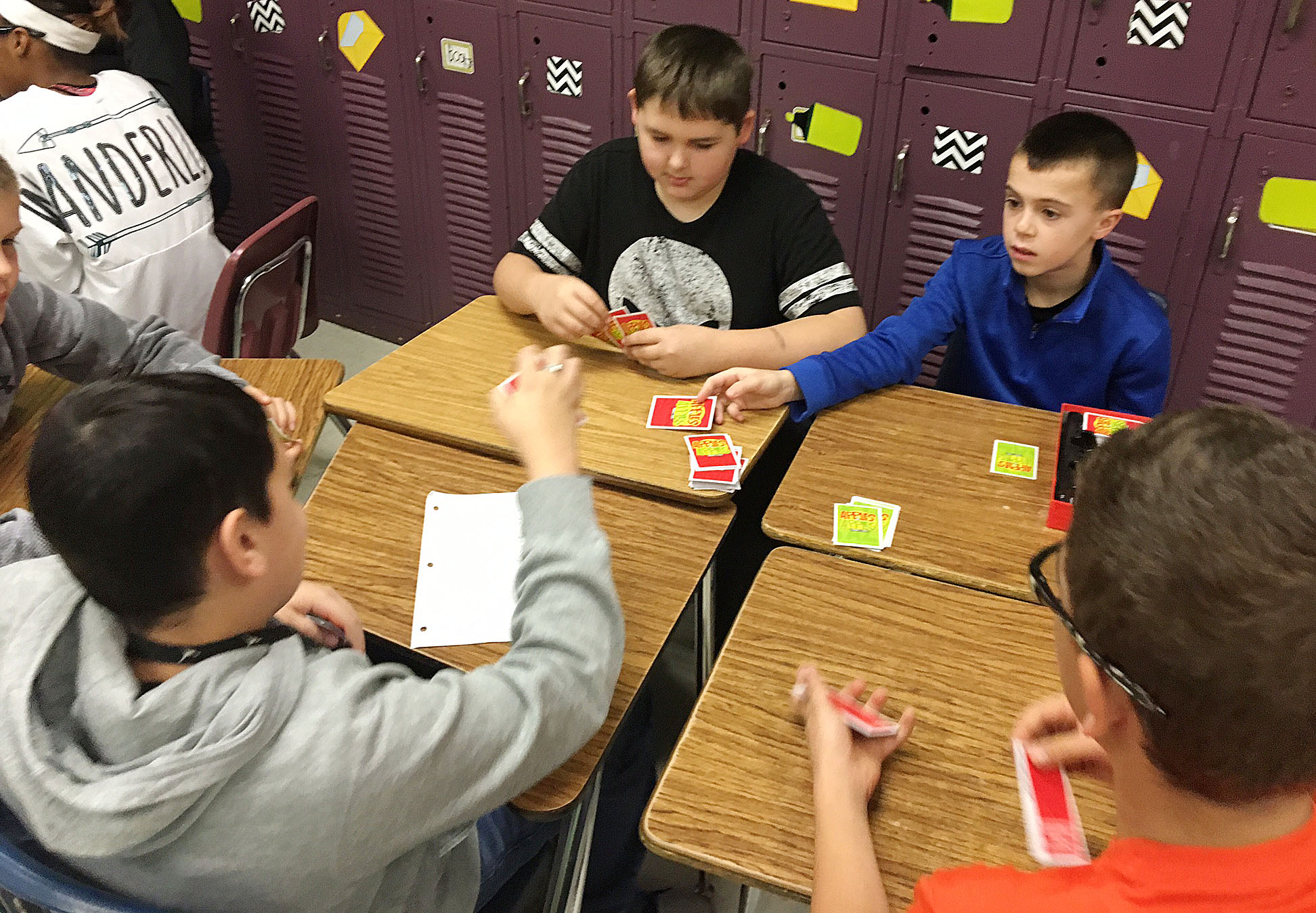 CMS seventh-grader Kaine Terry, at left, and sixth-grader Chase Hord play Apples to Apples with their classmates.