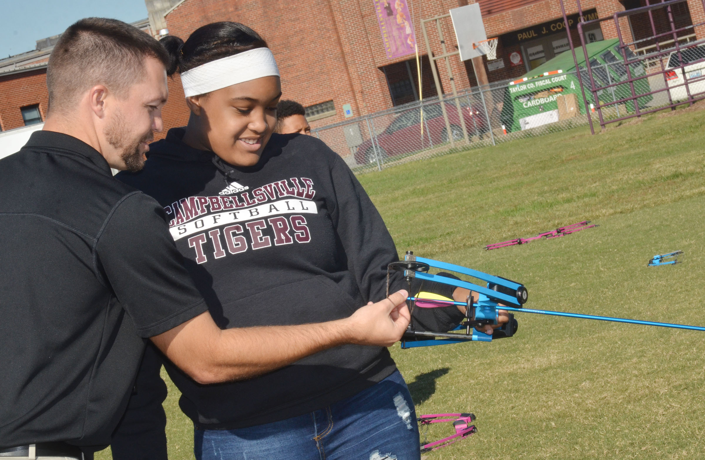 CMS physical education teacher Weston Jones helps eighth-grader Kelsey King load an arrow.