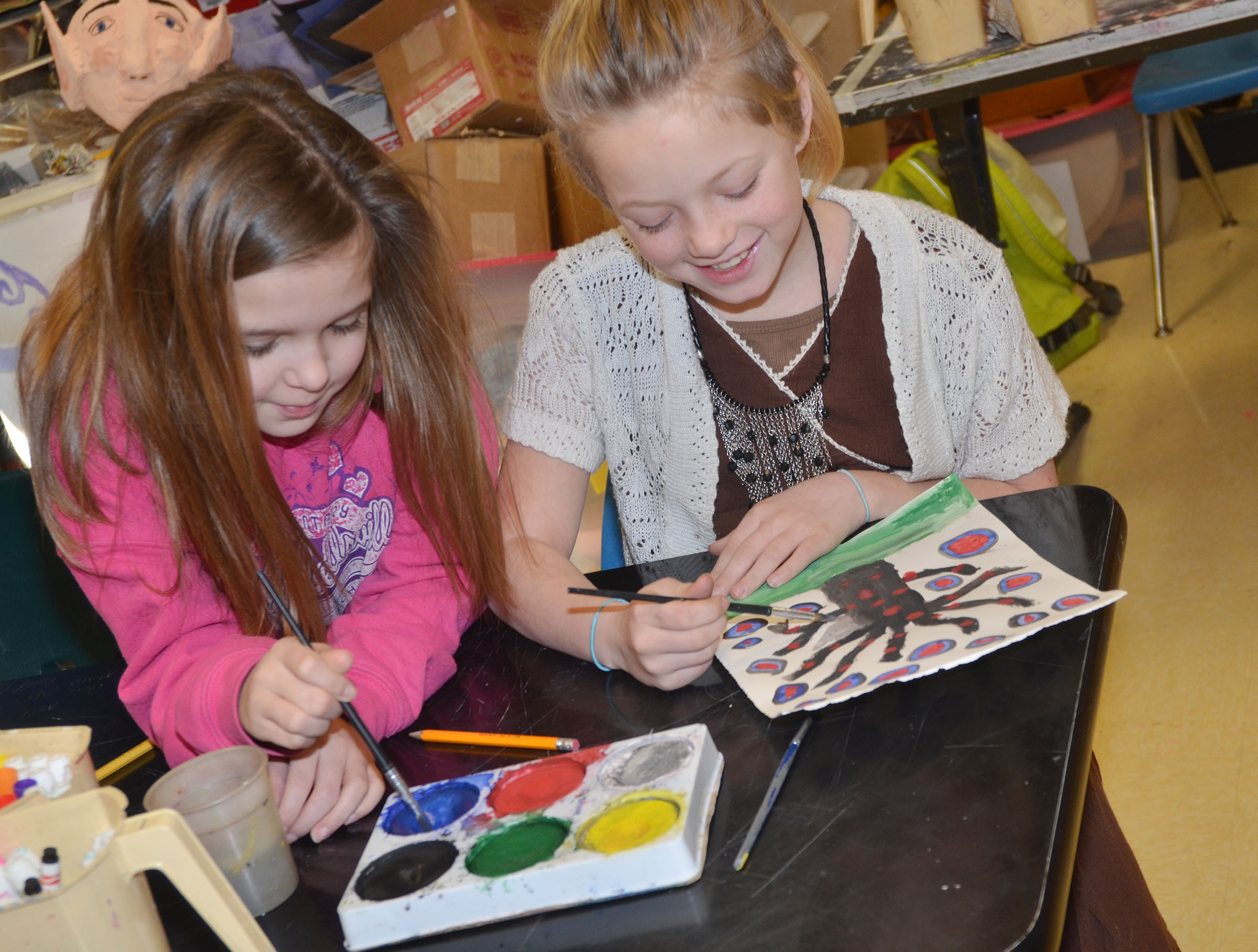CMS fourth-graders Natasha Torres, at left, and Kyra Parker work on their concentric circle paintings.