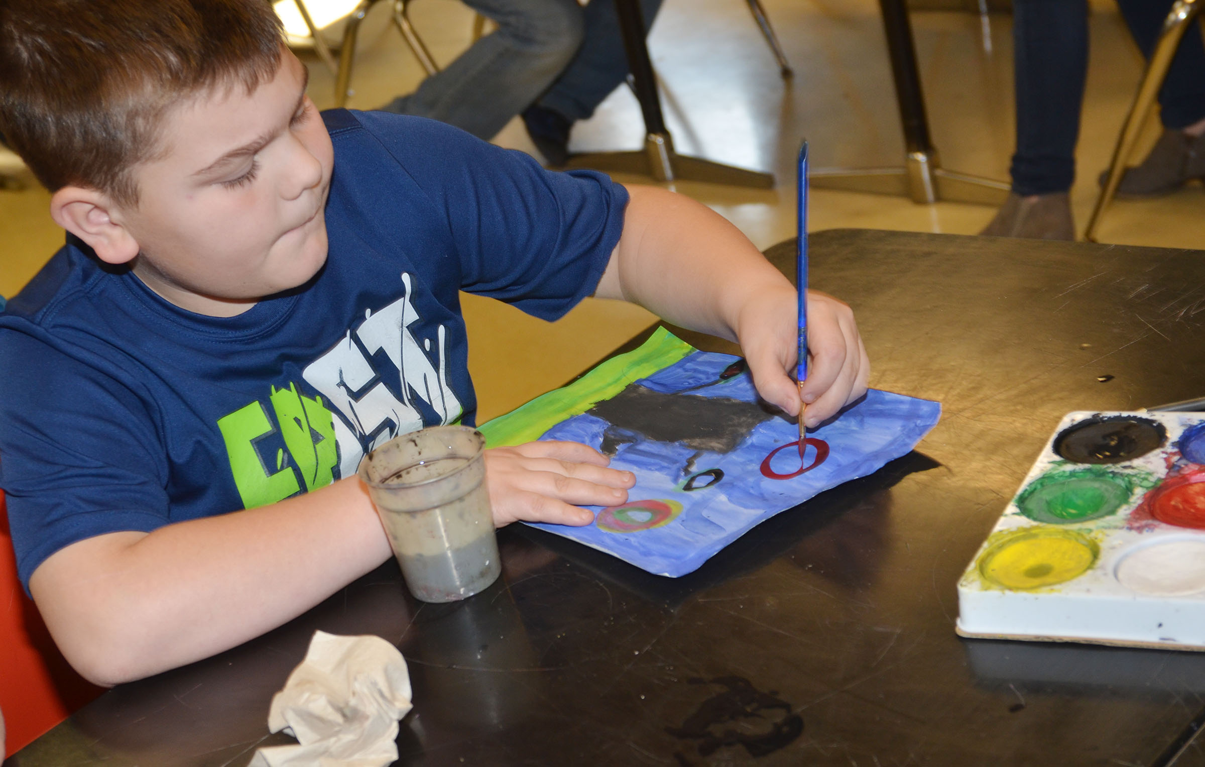 CMS fourth-grader Logan England paints his concentric artwork.