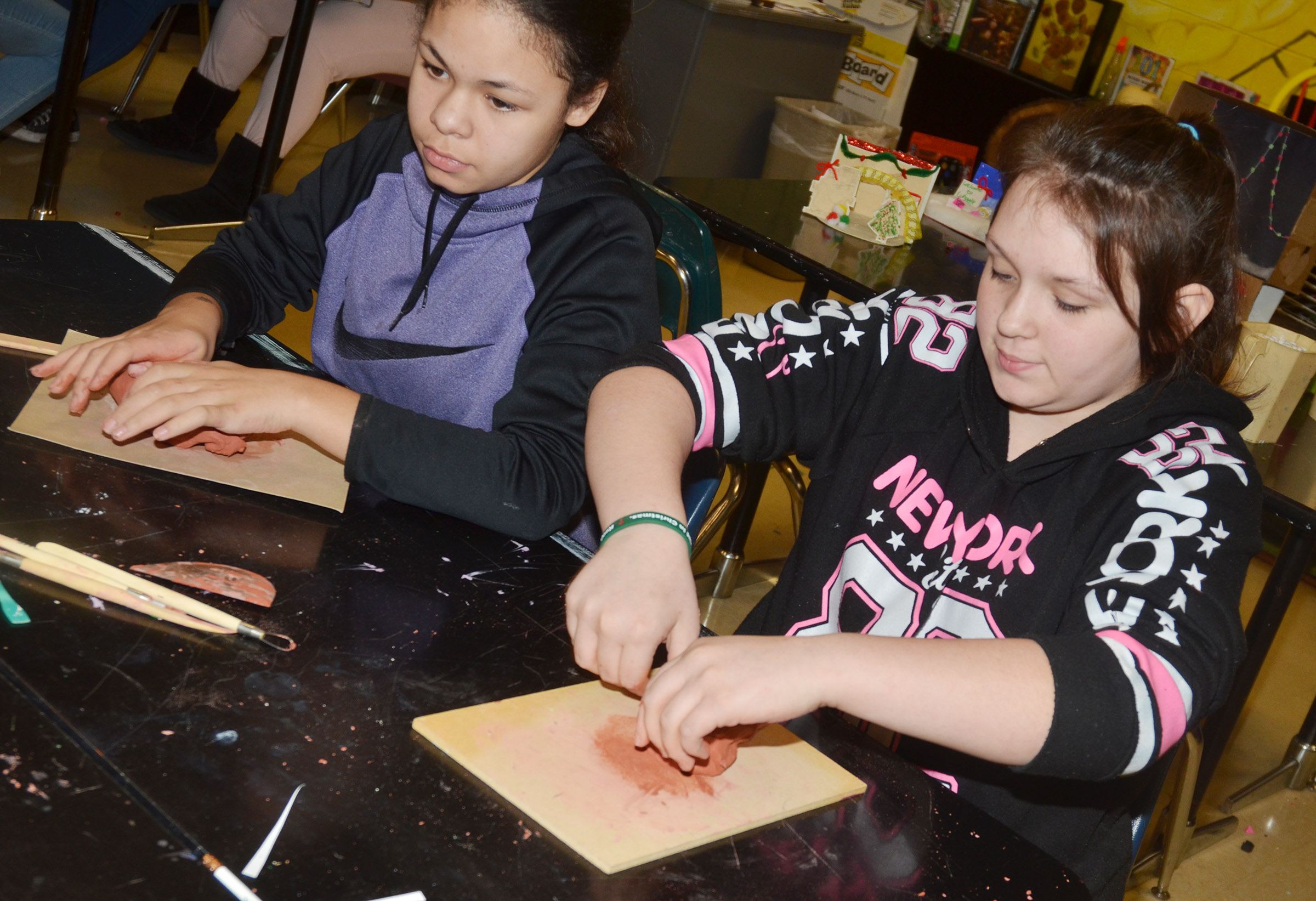 CMS sixth-graders Jayla Penn, at left, and Allie Compton work with clay.