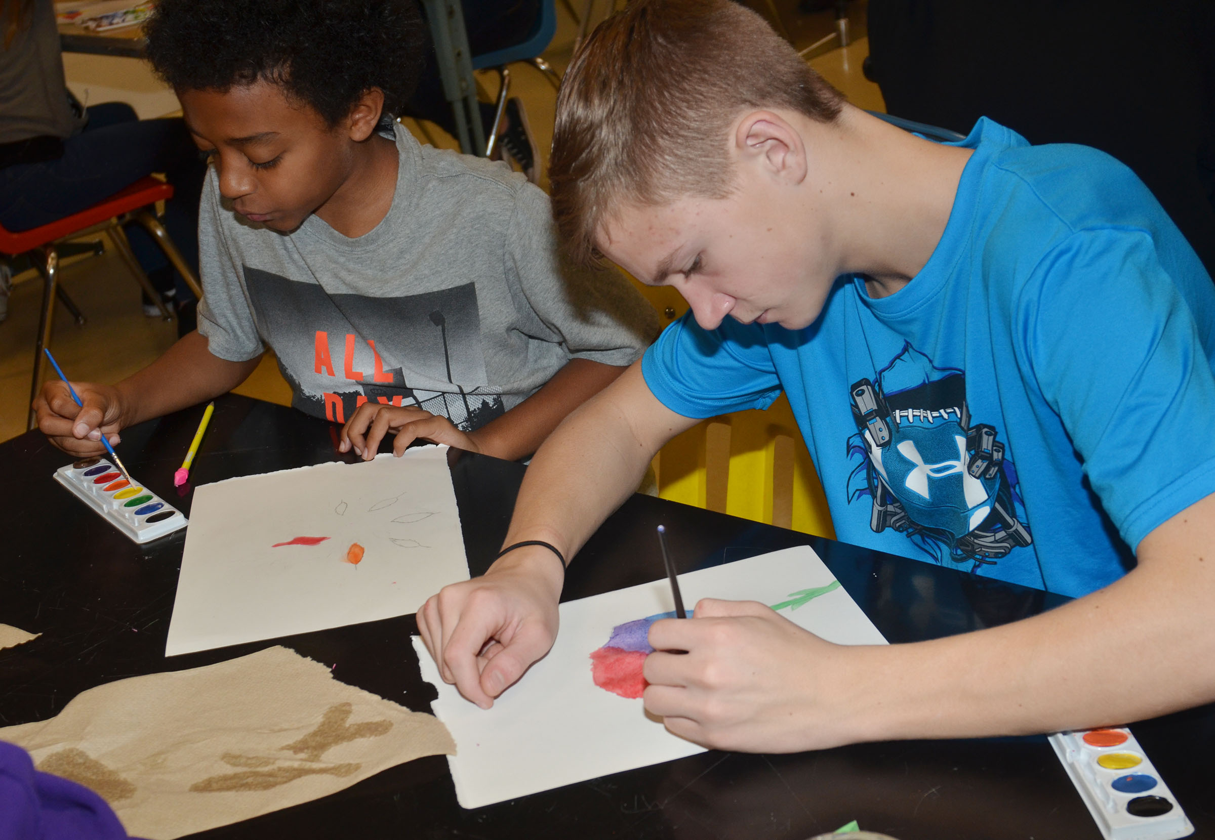 CMS sixth-grader Zamar Owens, at left, and eighth-grader Blase Wheatley paint their color wheel designs.