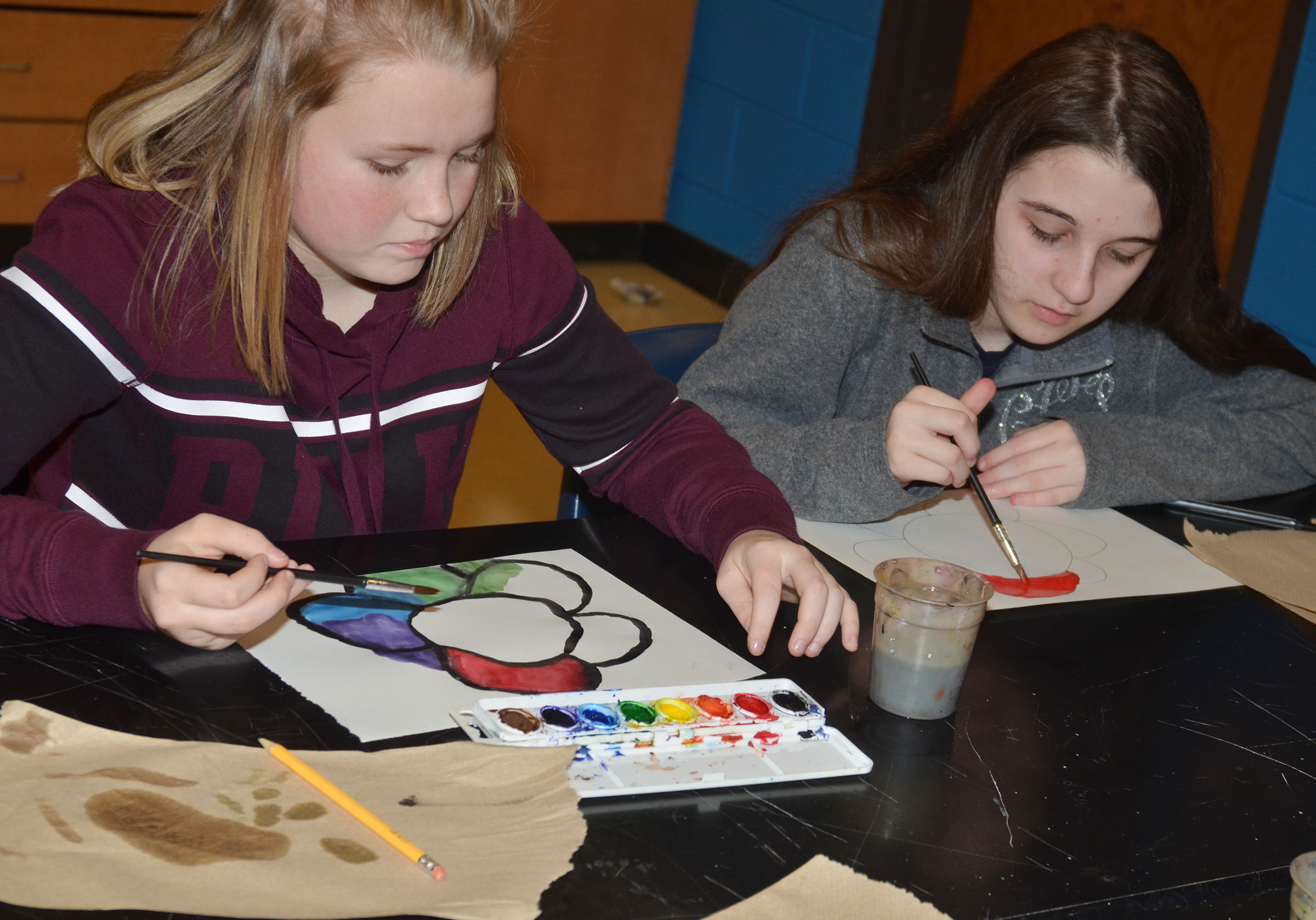 CMS eighth-graders Alanna Atwood, at left, and Chloe Cox paint their color wheel designs.