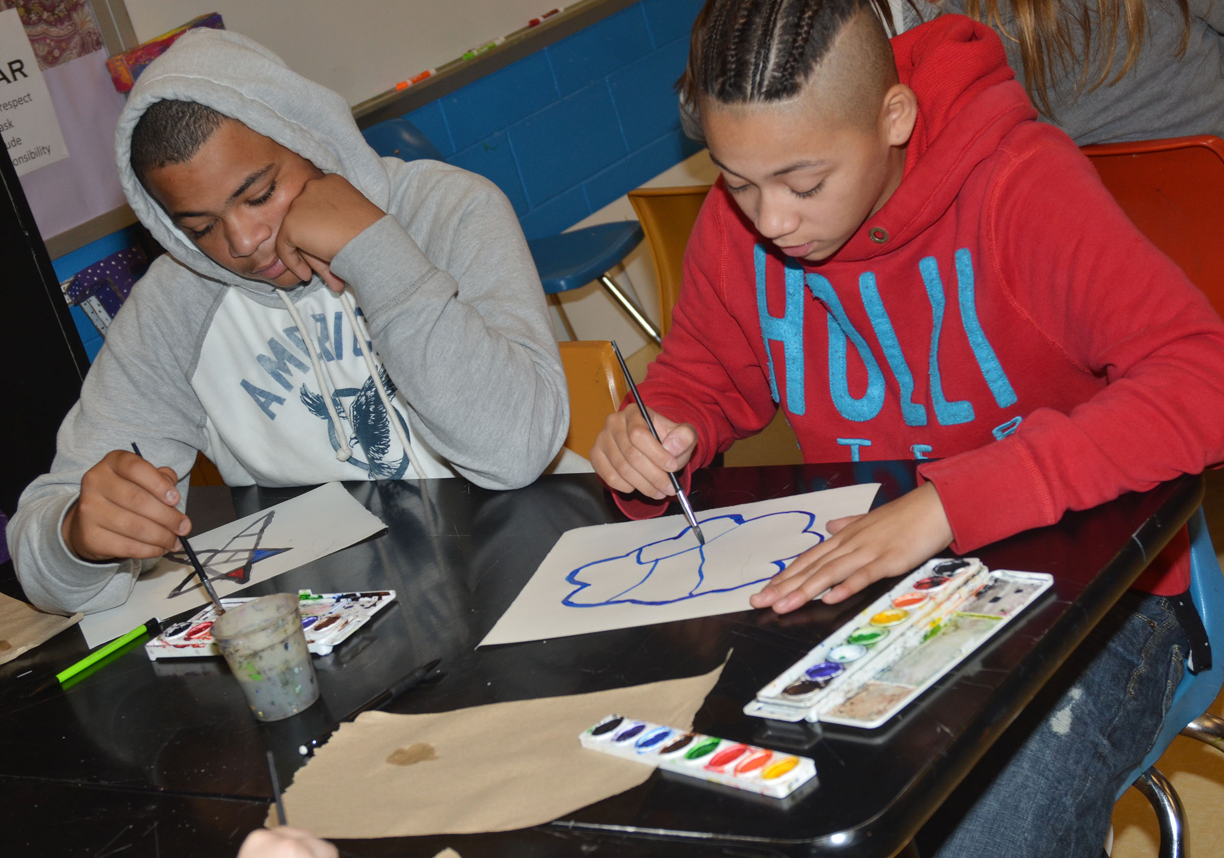 CMS seventh-grader Darious Groves, at left, and eighth-grader Taylor Whaley paint their color wheel designs.