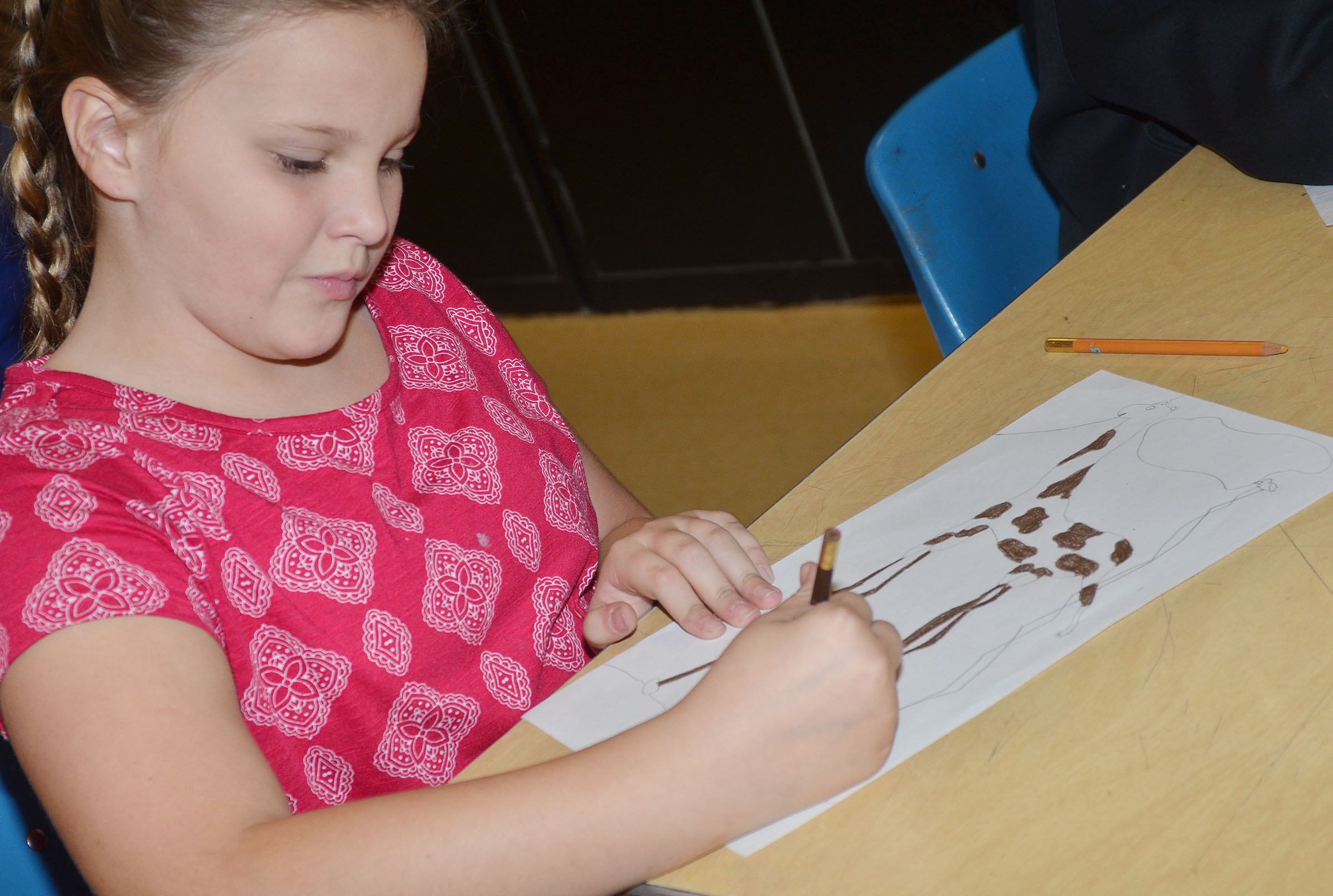 CMS sixth-grader Graci Crews colors her animal, drawn in Salvador Dali's style of surrealism.