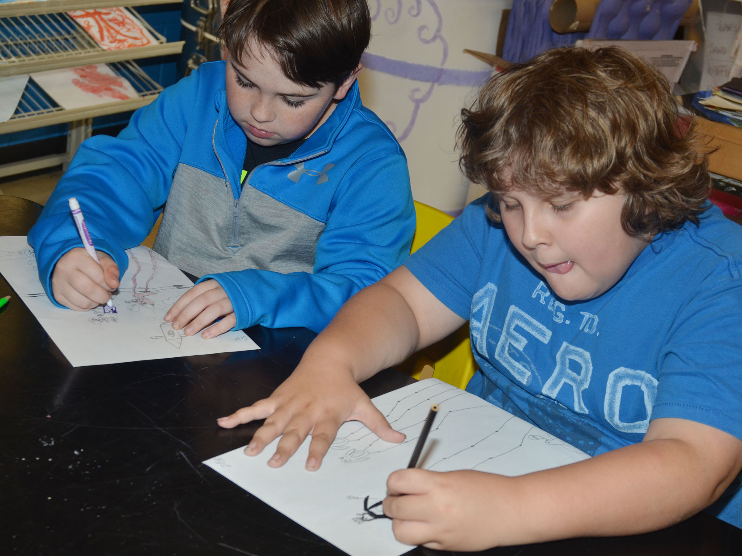 CMS fourth-graders Cody Agee, at left, and Zeke Harris draw their animals in Salvador Dali's style of surrealism.