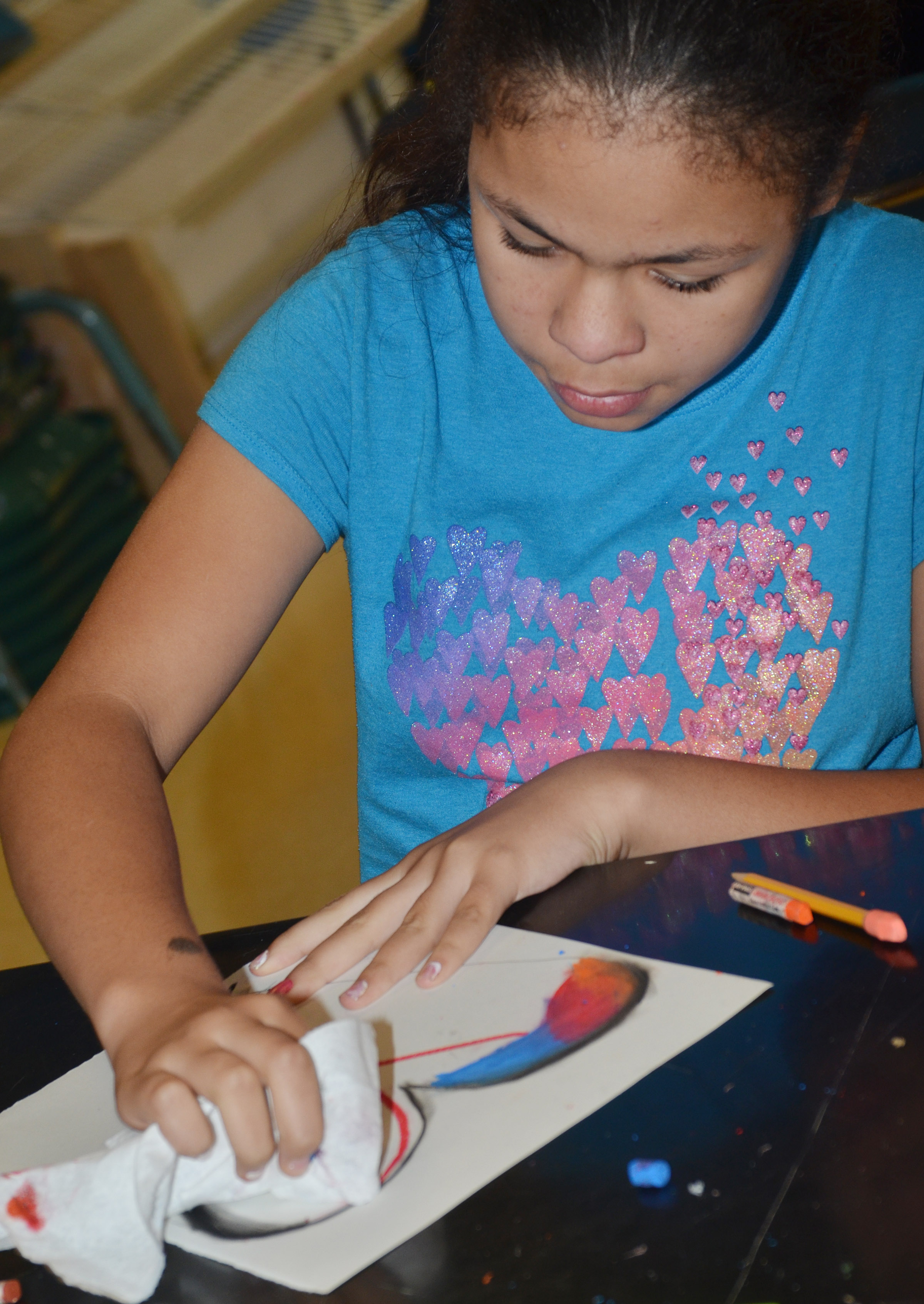 CMS sixth-grader Jayla Penn smooths her oil pastels.