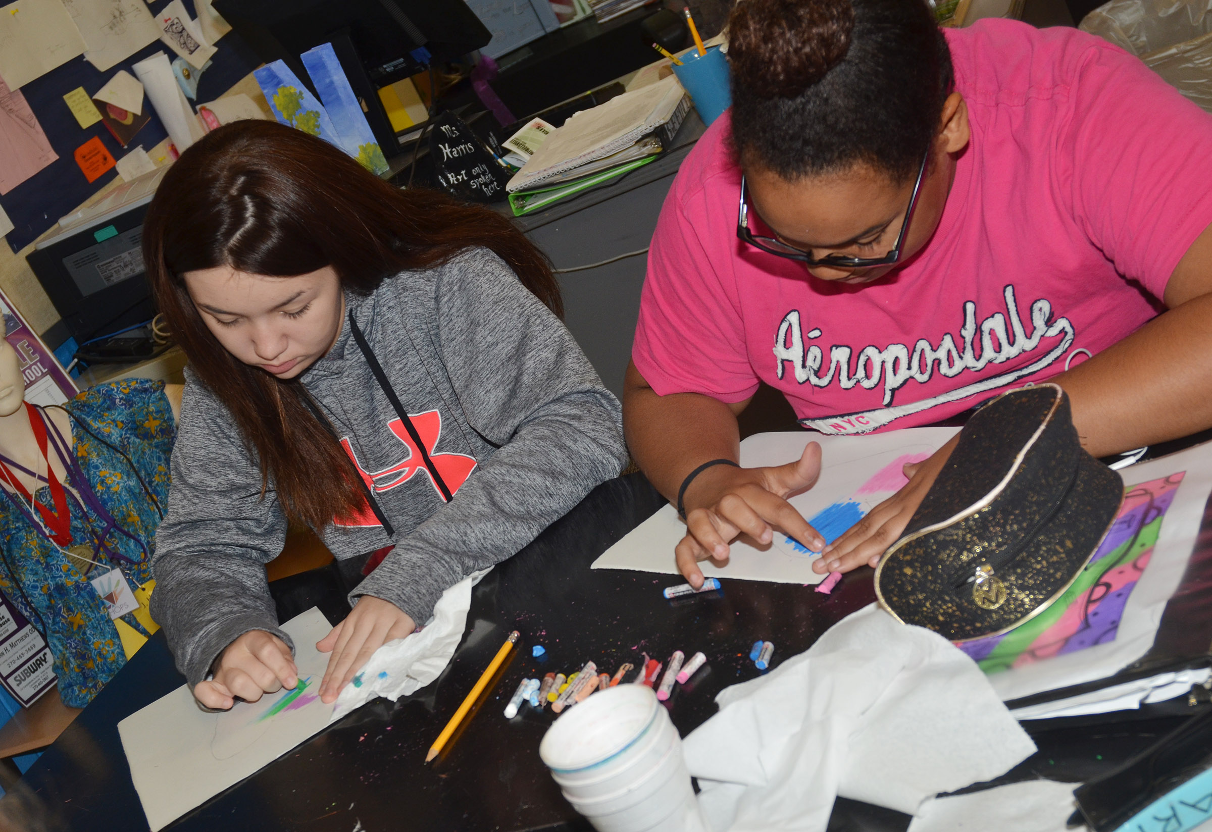 CMS eighth-graders Olivia Fields, at left, and Brae Washington add color to their hearts.