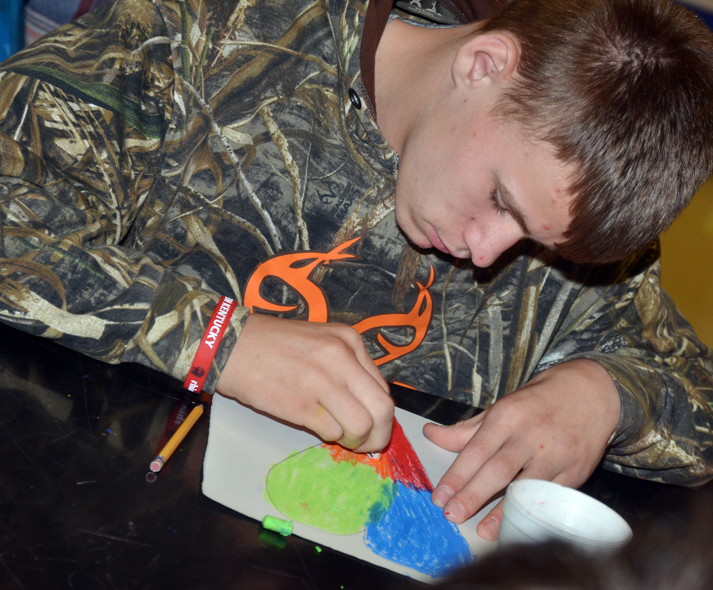 CMS eighth-grader Dalton Reynolds colors his heart with oil pastels.
