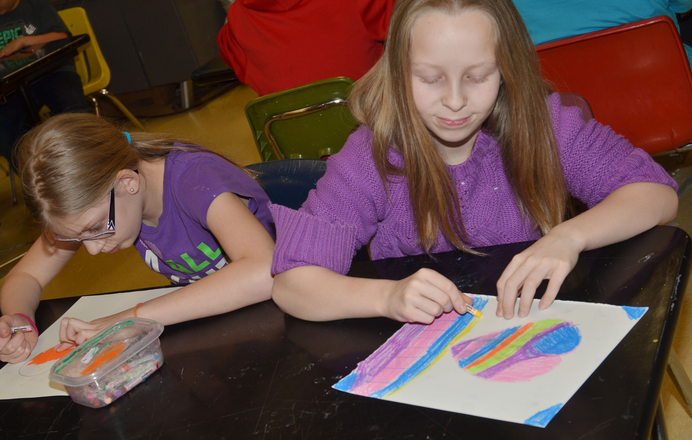 CMS fourth-graders Payton Releford, at left, and Lily Sallee color their hearts.