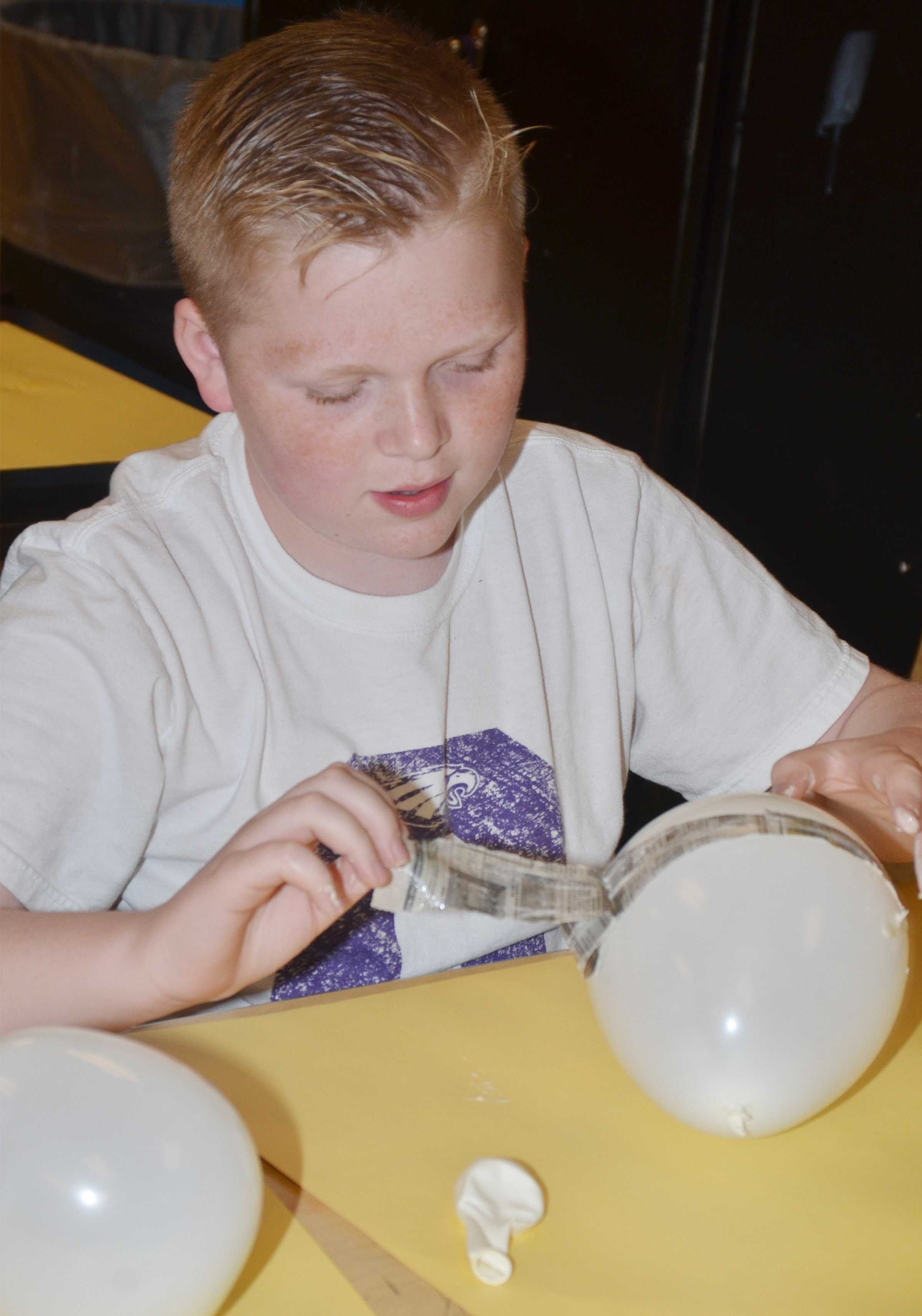 CMS fourth-grader Simon Wilkerson adds paper mache to his balloon, which will become a Faberge egg.