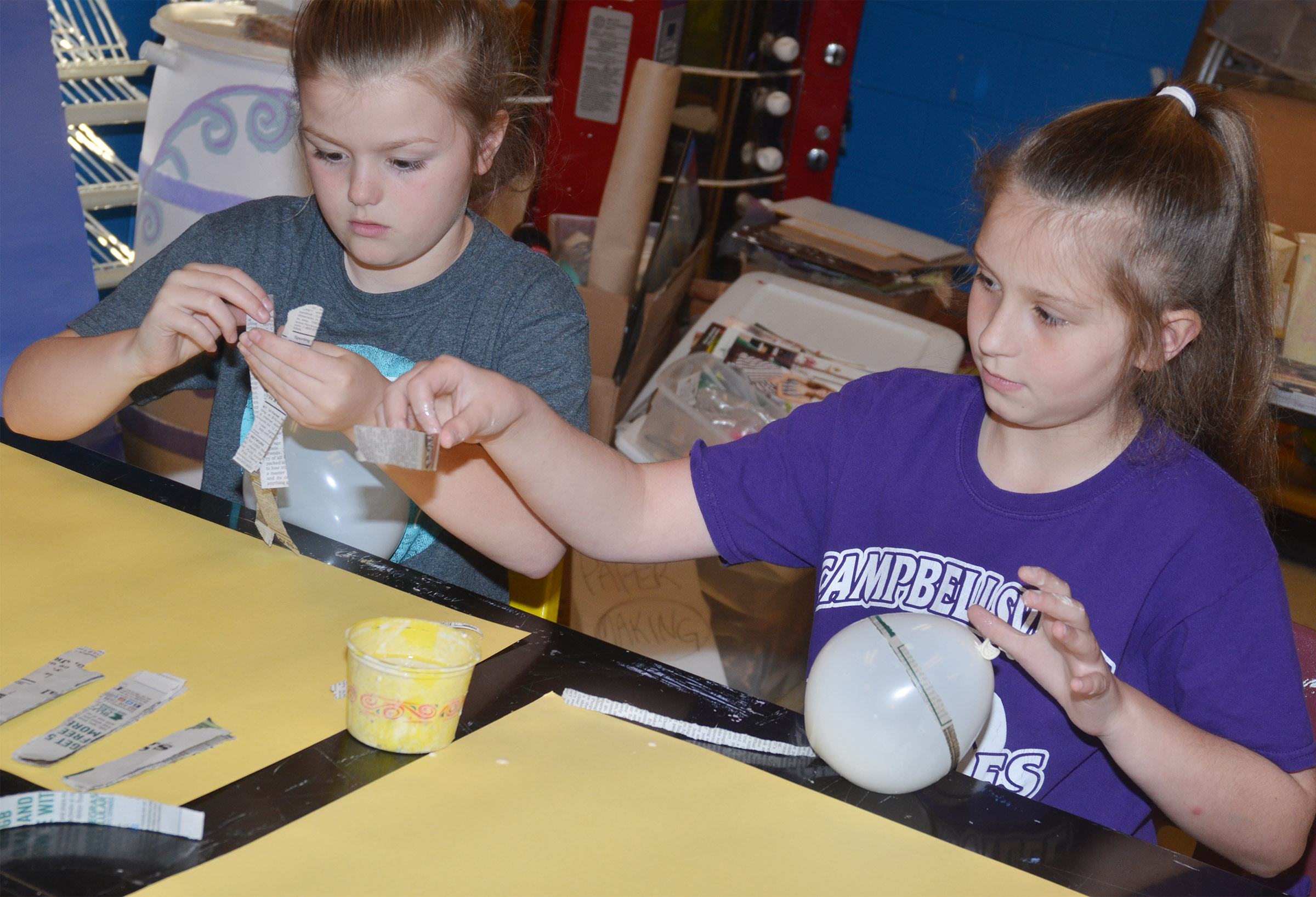 CMS fifth-graders Ellington Gowin, at left, and Mollie Bailey add paper mache to their balloons, which will become Faberge eggs.