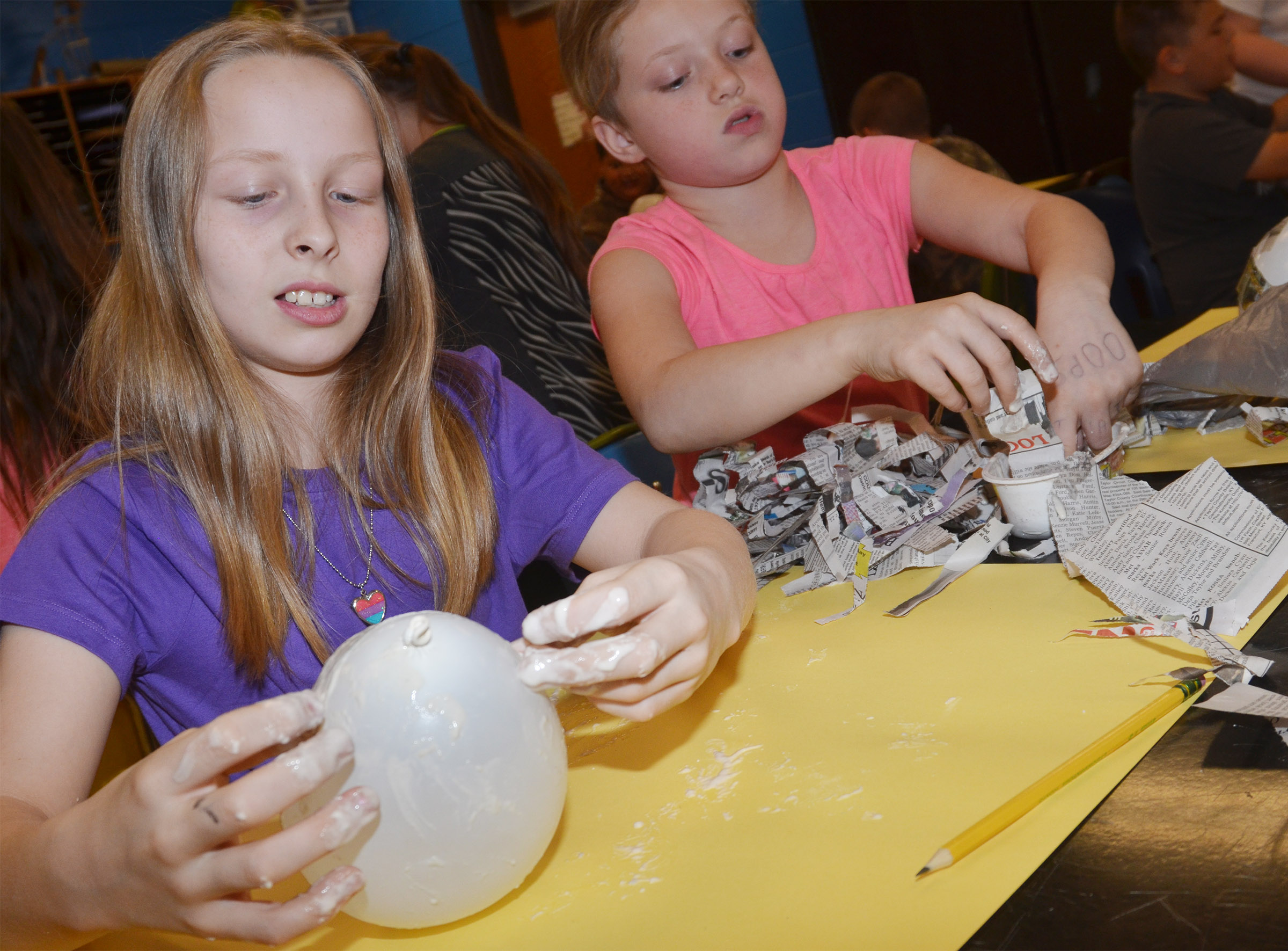 CMS fourth-graders Lily Sallee, at left, and Kyra Parker add paper mache to their balloons, which will become Faberge eggs.