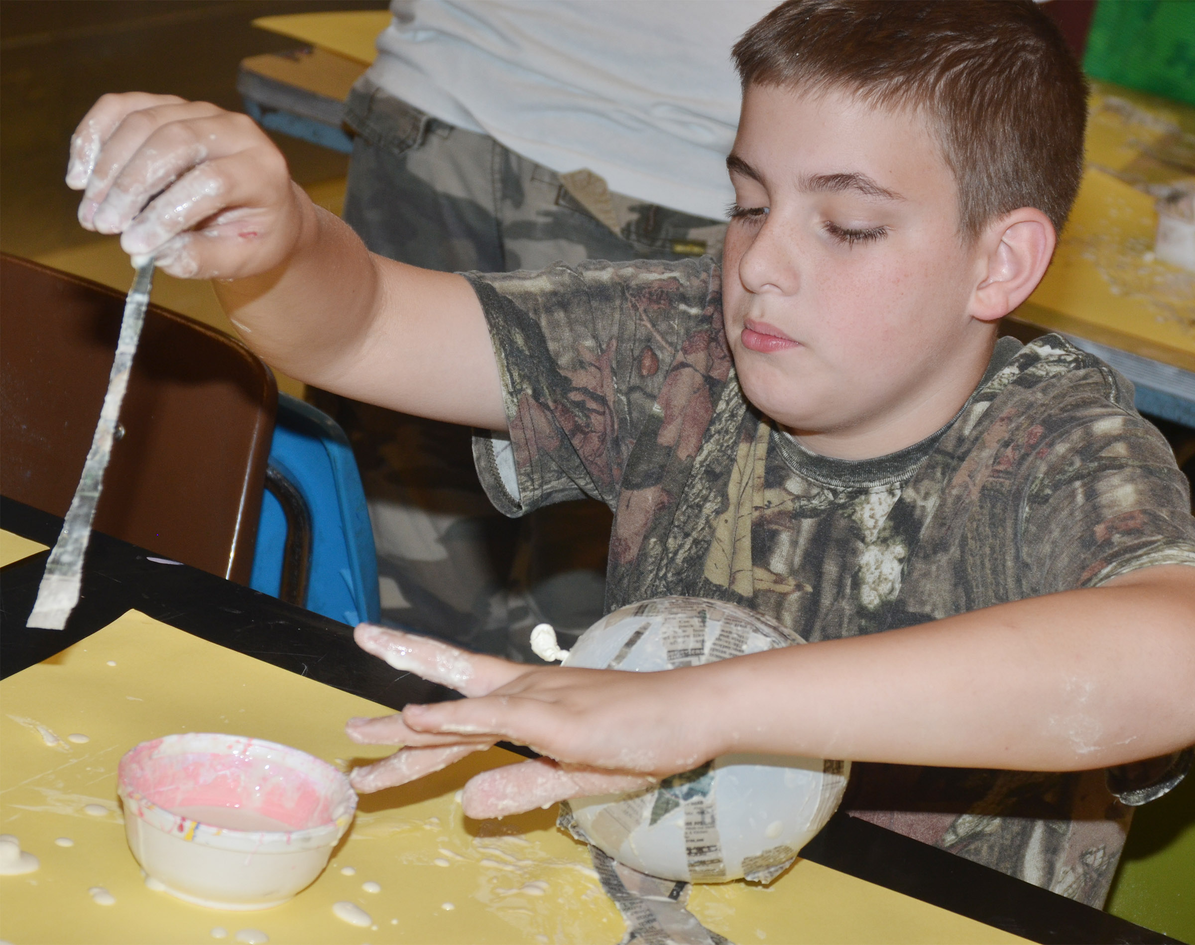 CMS fifth-grader Ashton Davis adds paper mache to his balloon, which will become a Faberge egg.