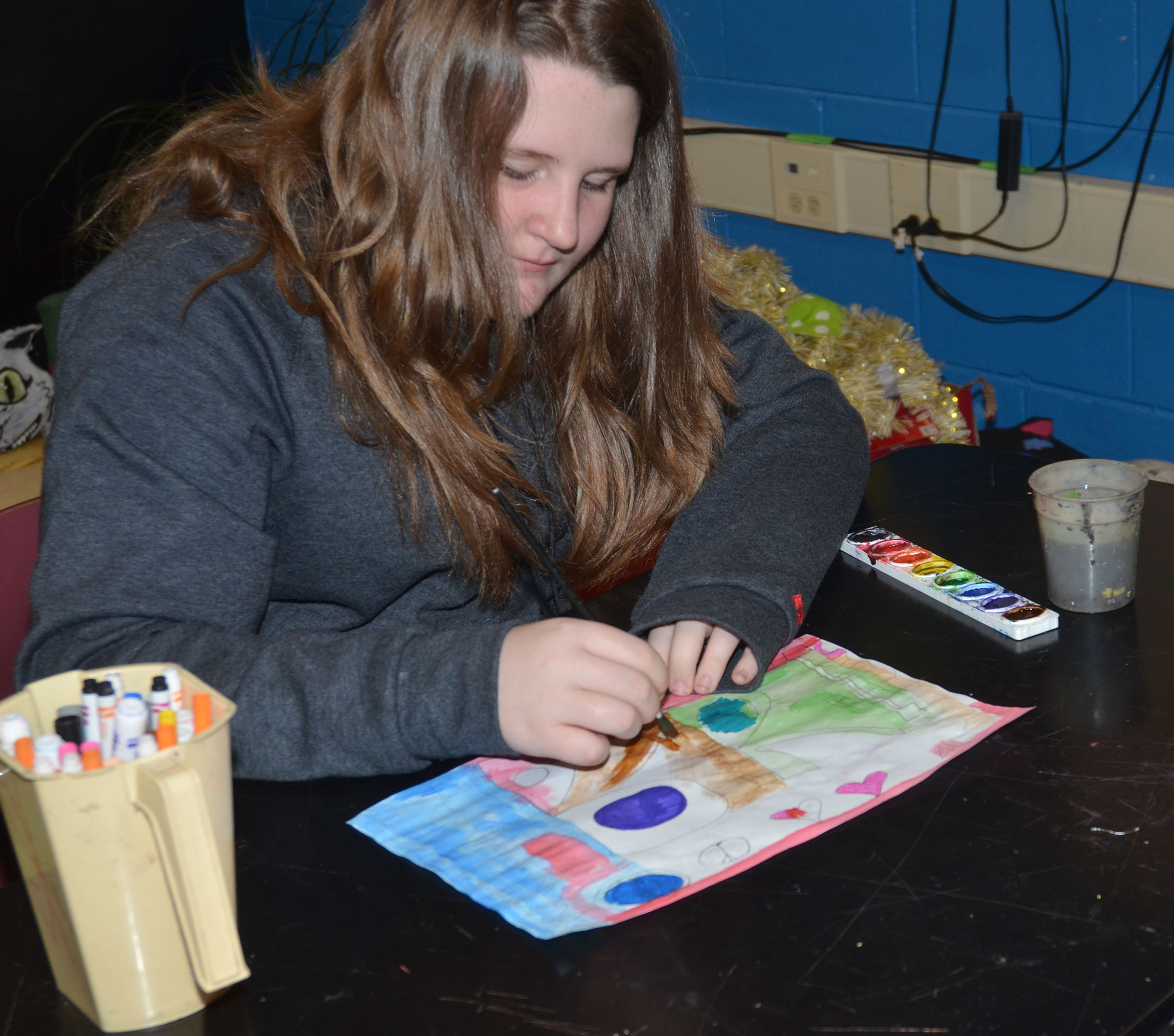 CMS seventh-grader Brittany Martin paints her graffiti tag with watercolors.