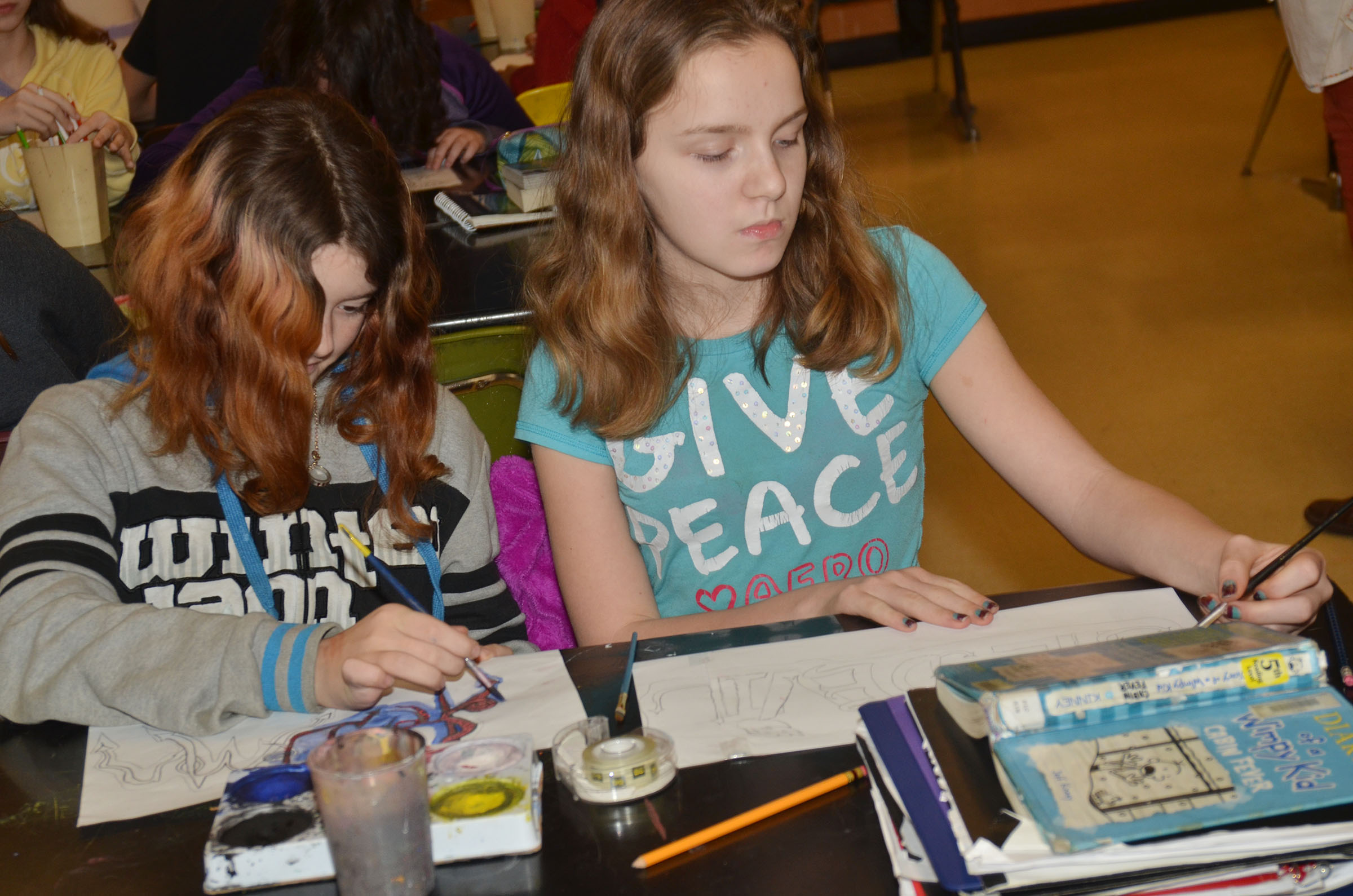 CMS sixth-graders Leah Parker, at left, and Adrianna Sluder paint their graffiti tags.