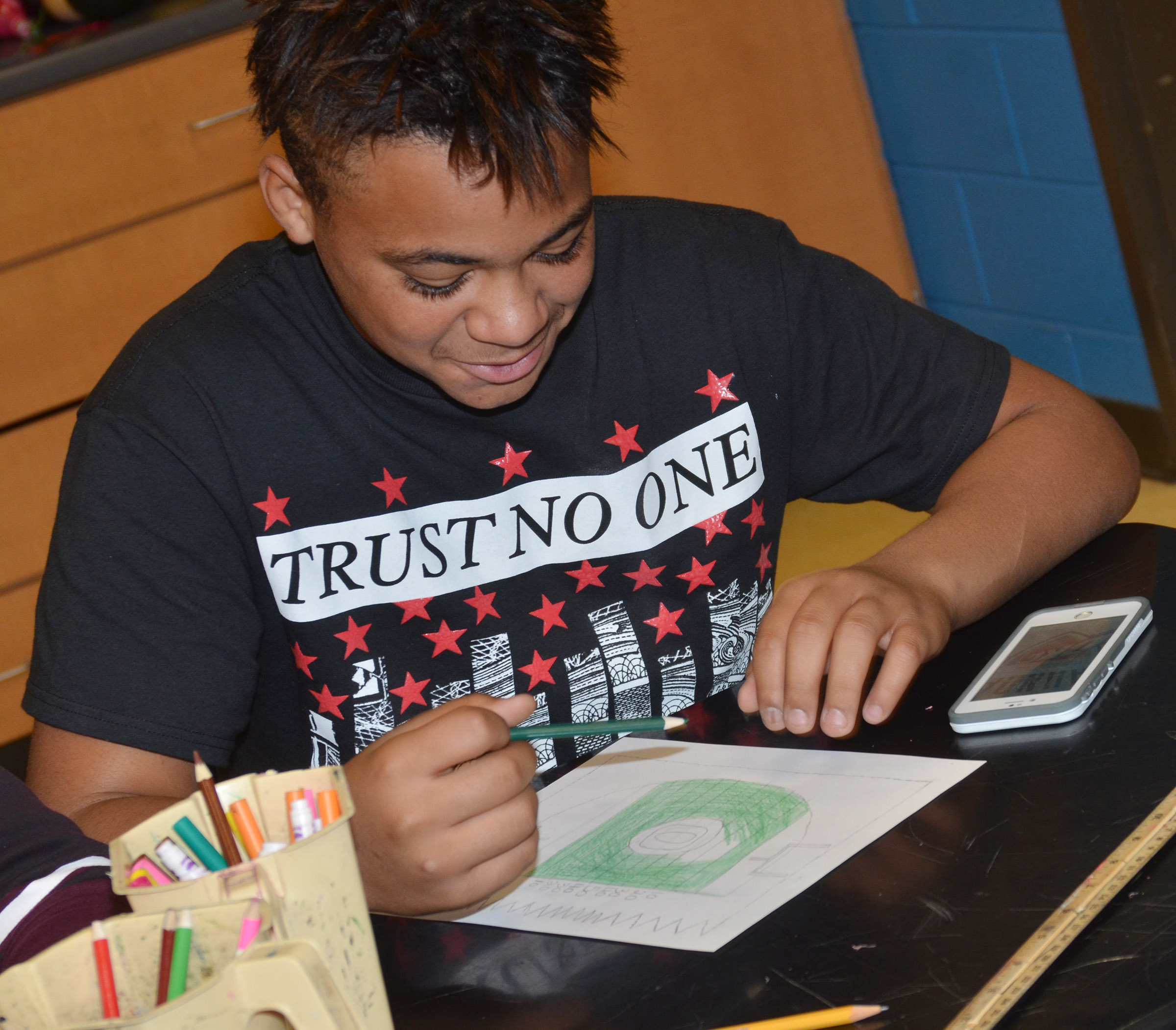 CMS seventh-grader Darious Groves colors his illuminated letter, which was drawn as a football field.