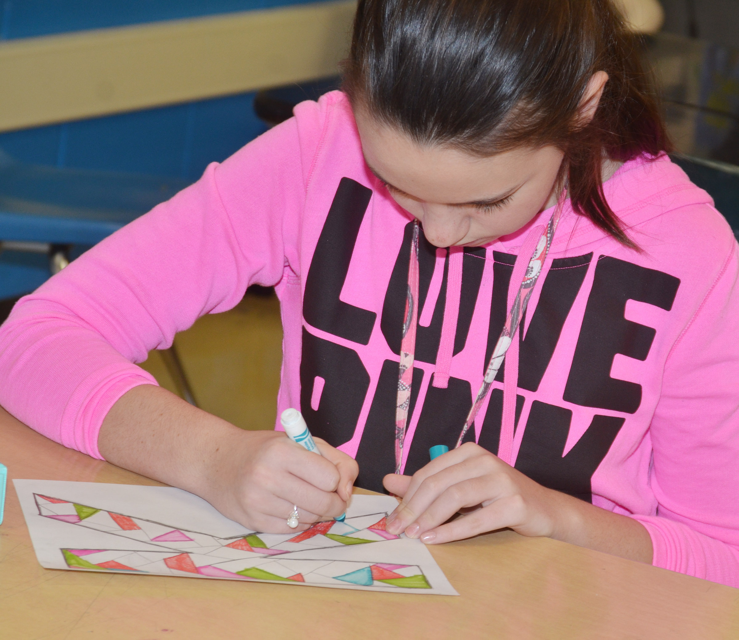 CMS seventh-grader Karley Morris colors her illuminated letter, which features many colors and designs.