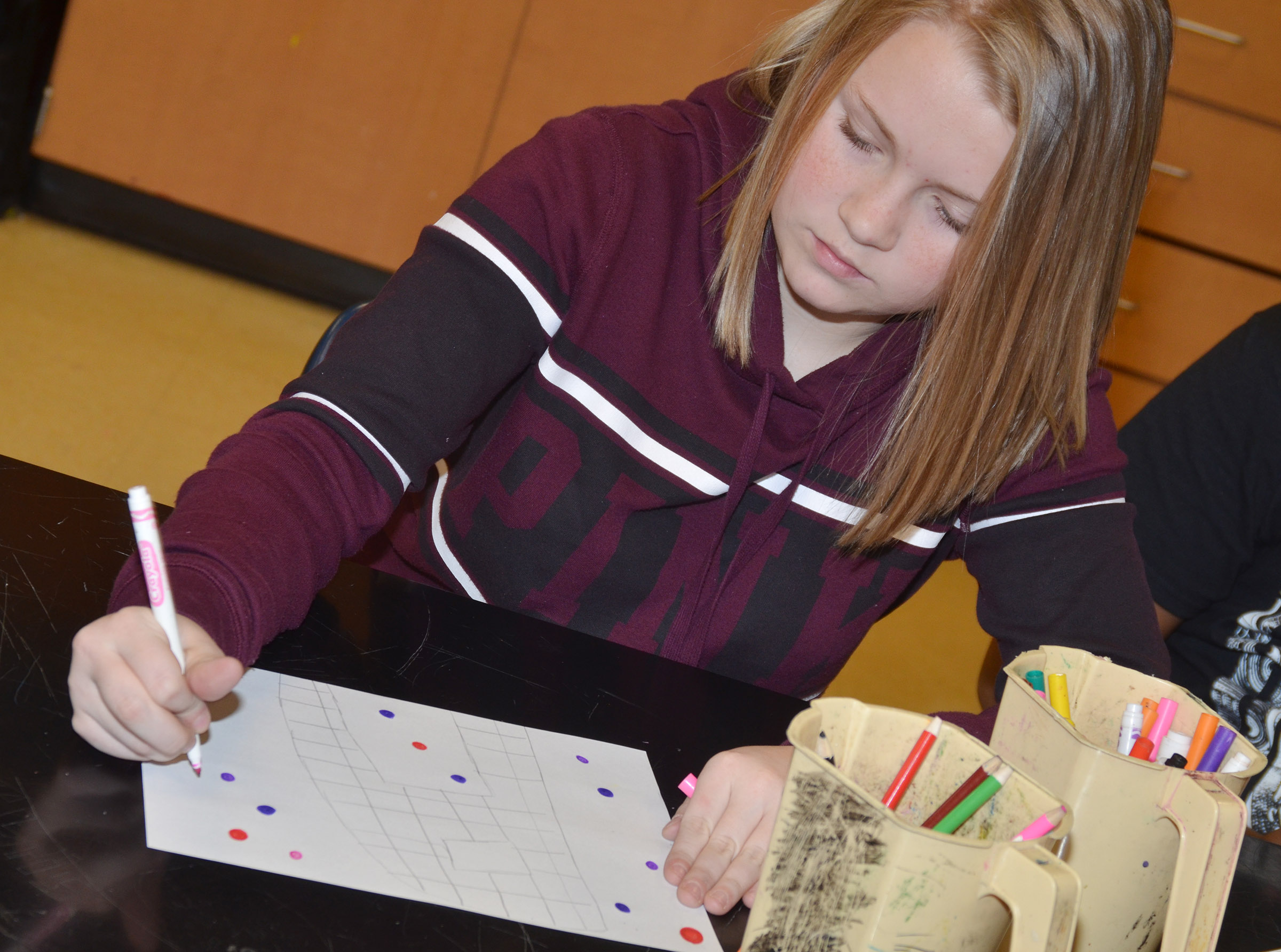 CMS eighth-grader Alanna Atwood colors her illuminated letter, which features many different designs.