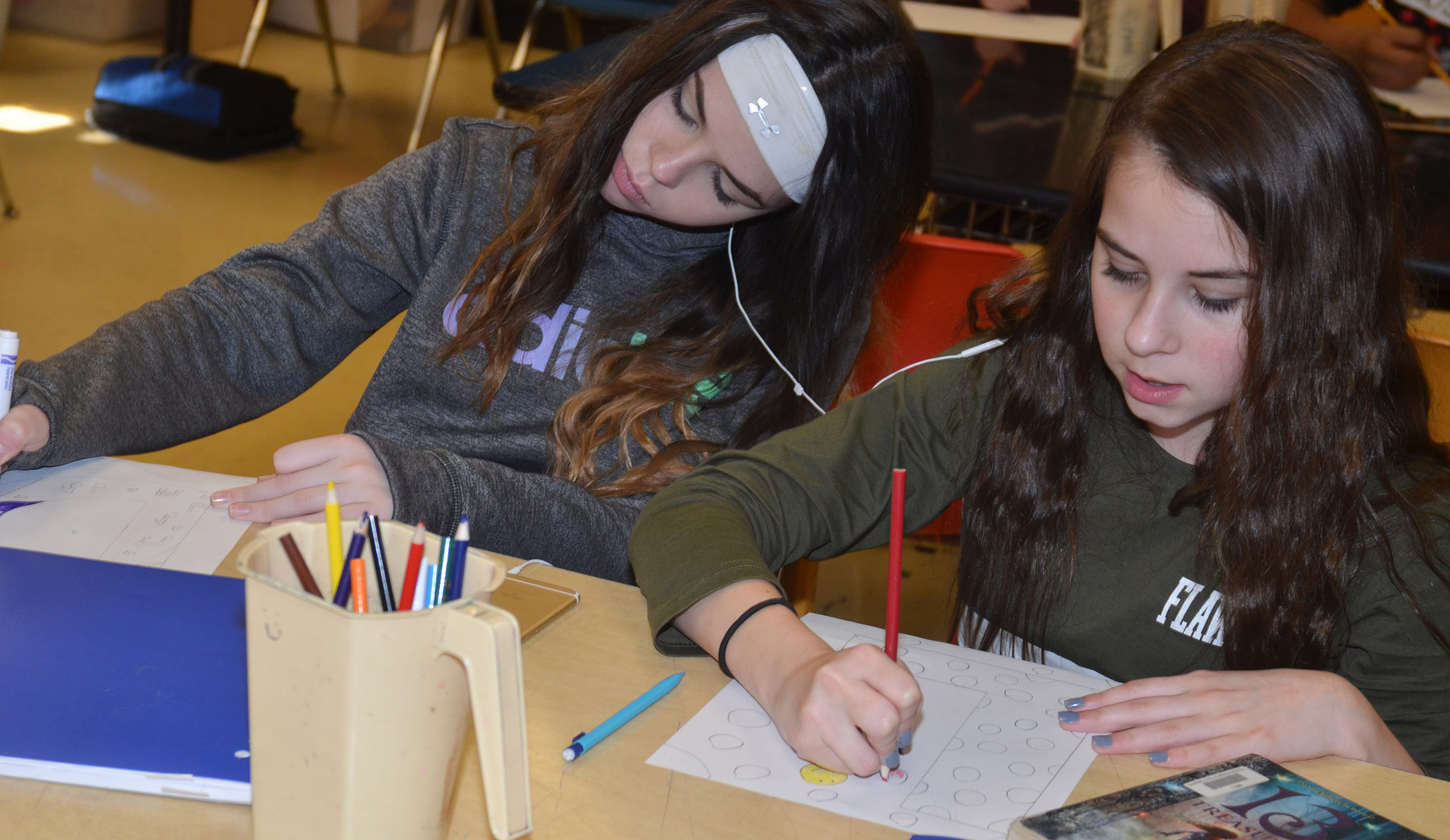 CMS seventh-grader Destiny Agee, at left, and Chloe Anderson color their illuminated letters.