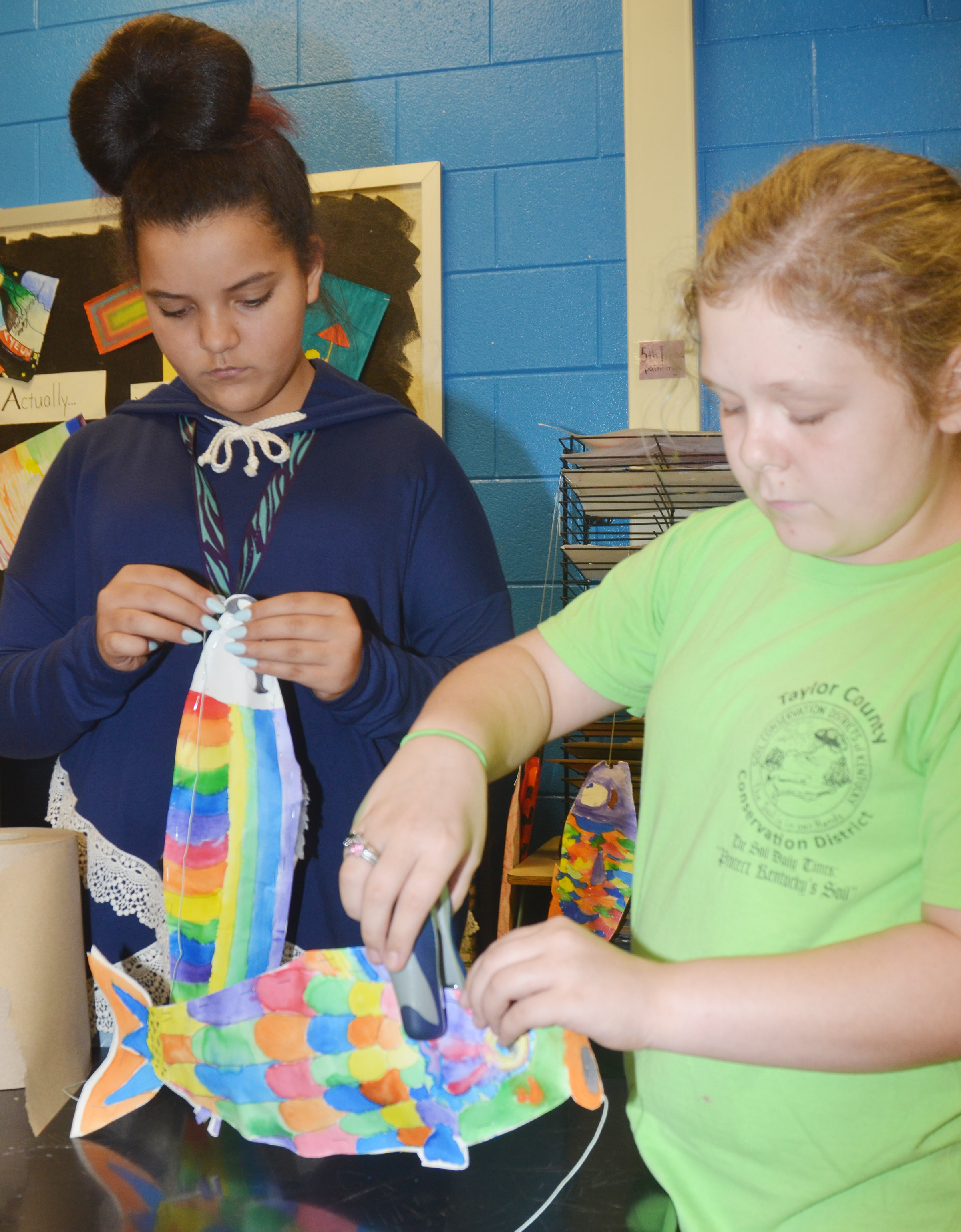CMS sixth-graders Gracie Taylor, at left, and Alexis Sharp staple their koinobori together.