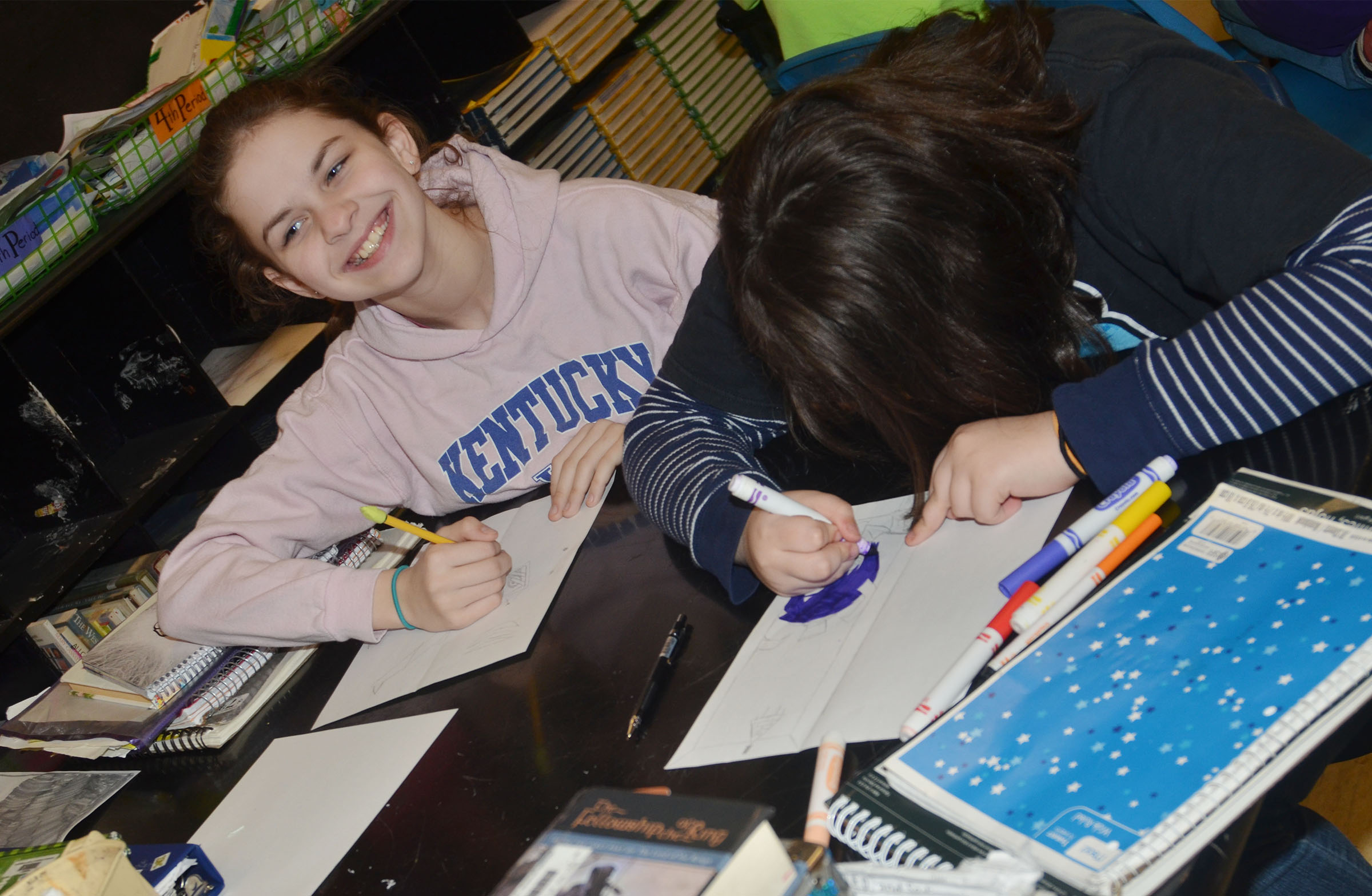 CMS sixth-grader Karlee Rakel, at left, and eighth-grader Haley Lopez draw the imaginary worlds inside their lockers.